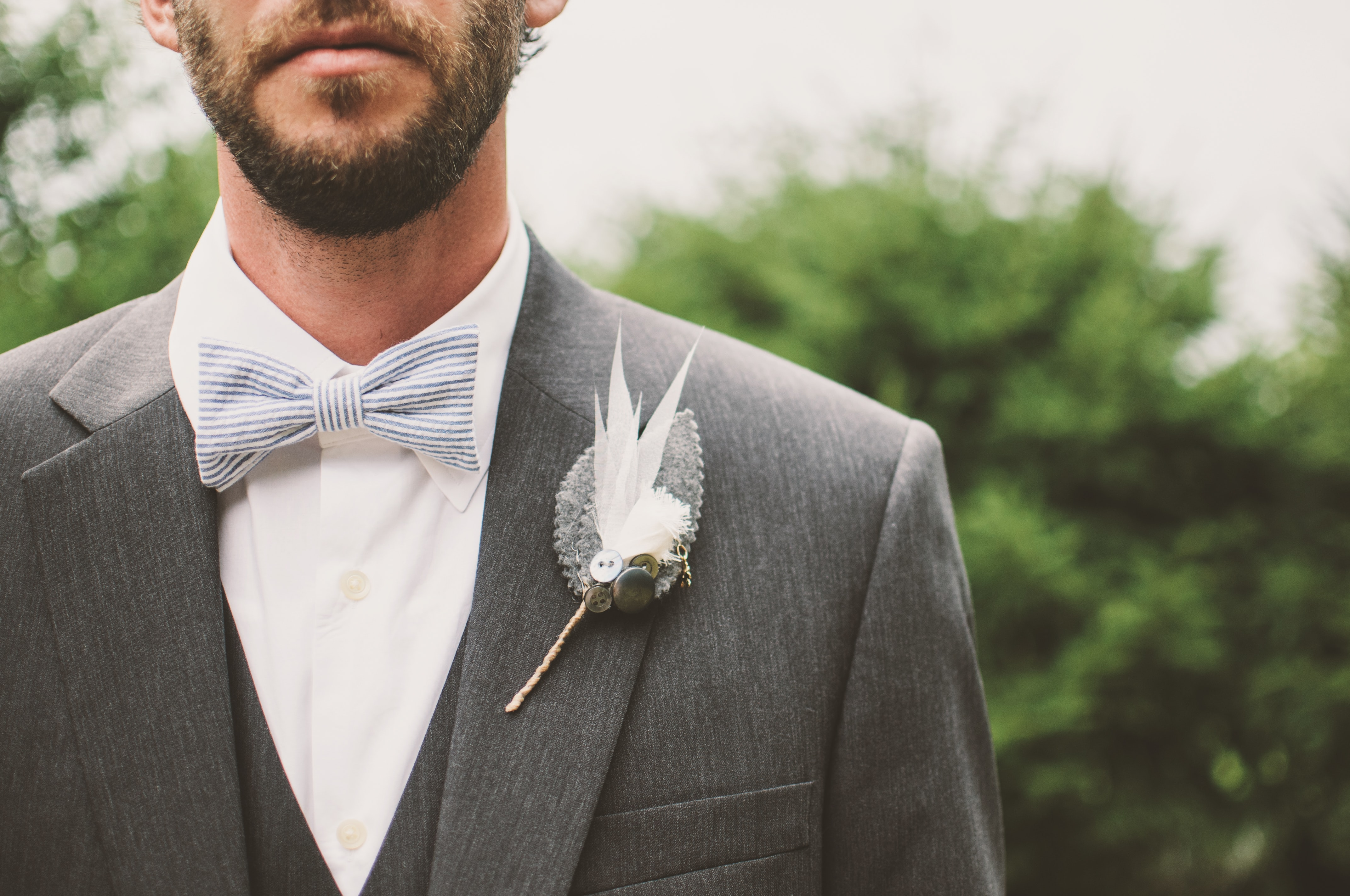 A bearded groom wearing a gray suit and striped bowtie with a unique boutonniere