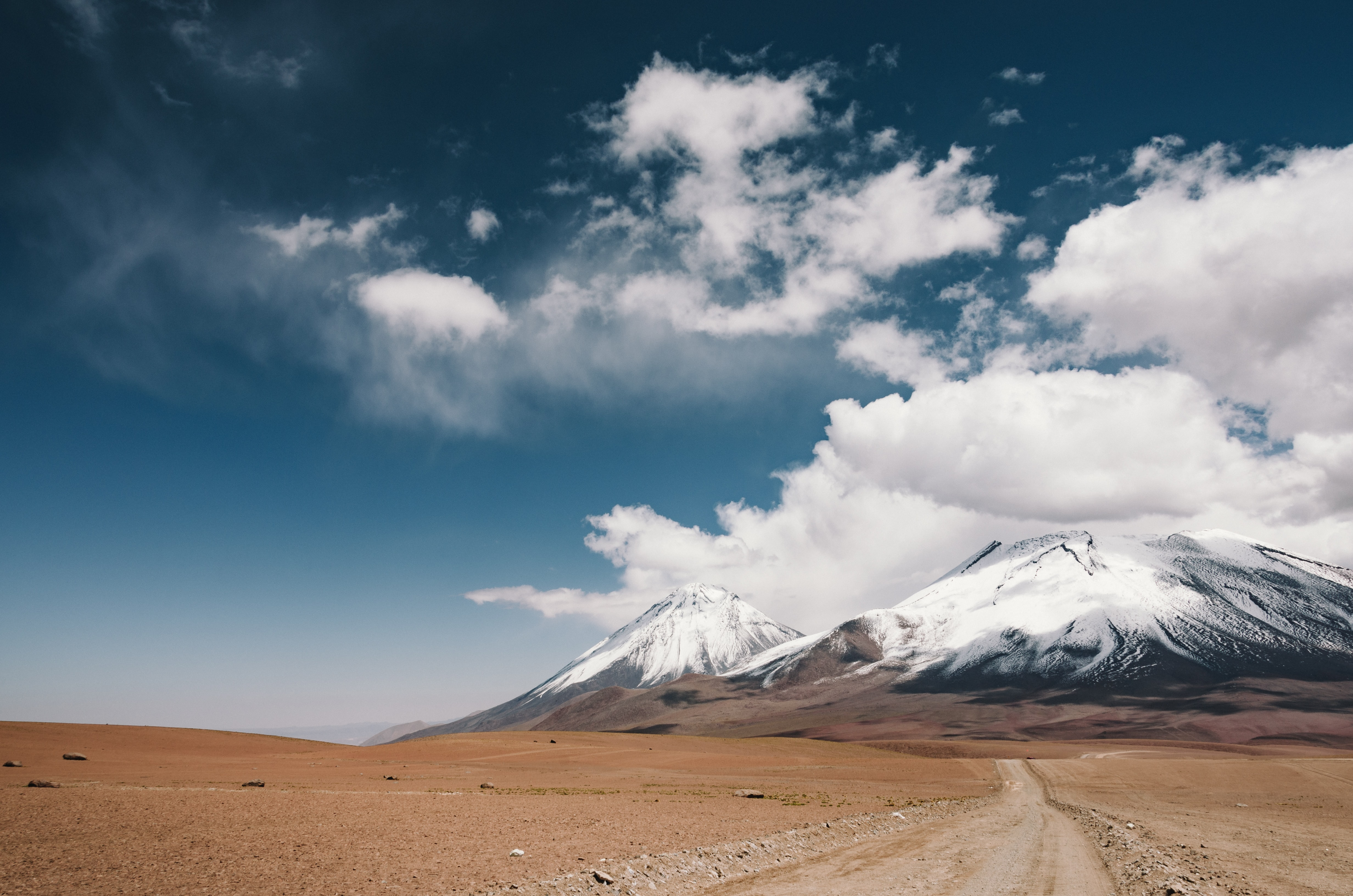 Road in the plains leading to cloud-covered snowy mountains in Licancabur