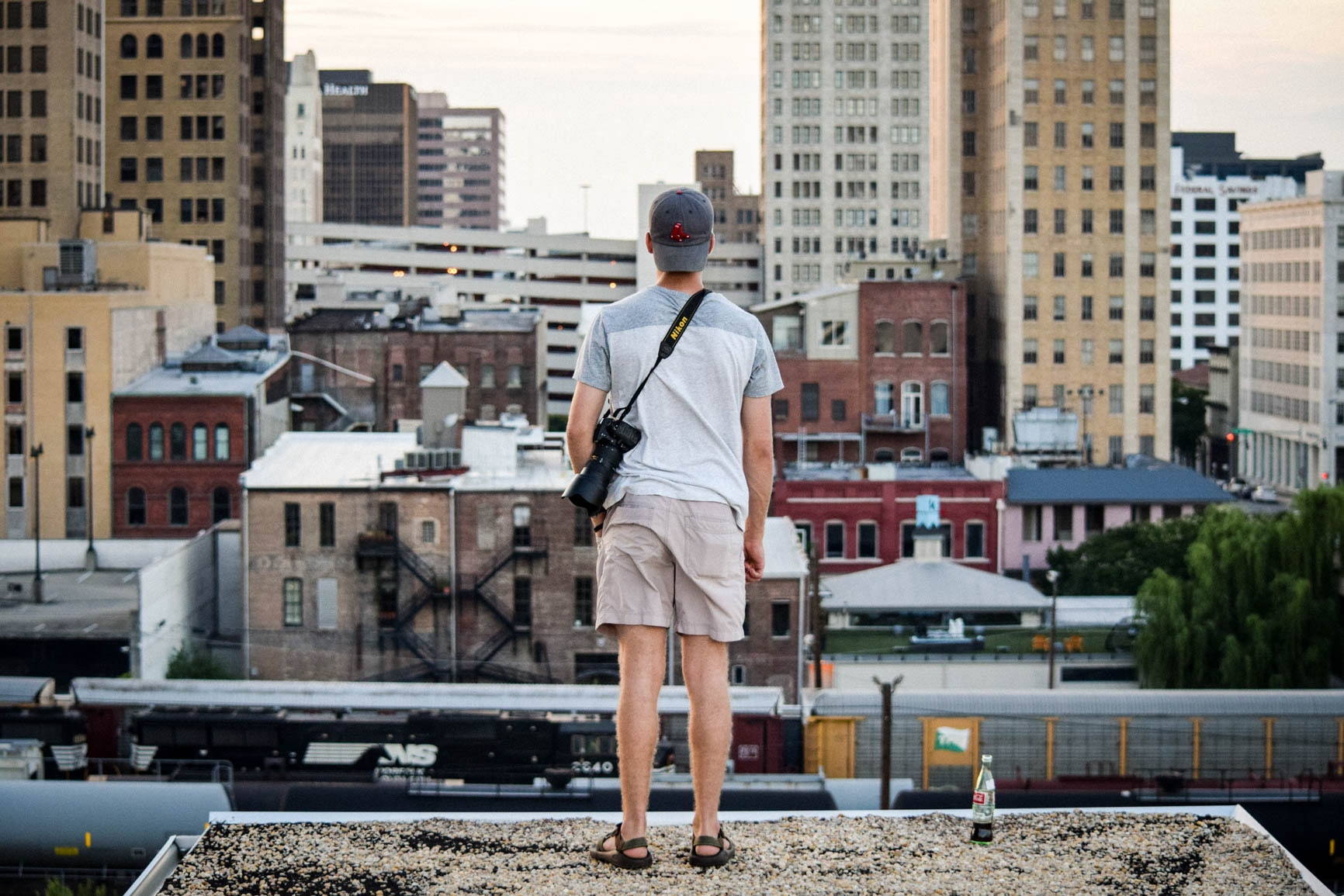 A person in a backwards cap with a camera stands on a rooftop overlooking a city