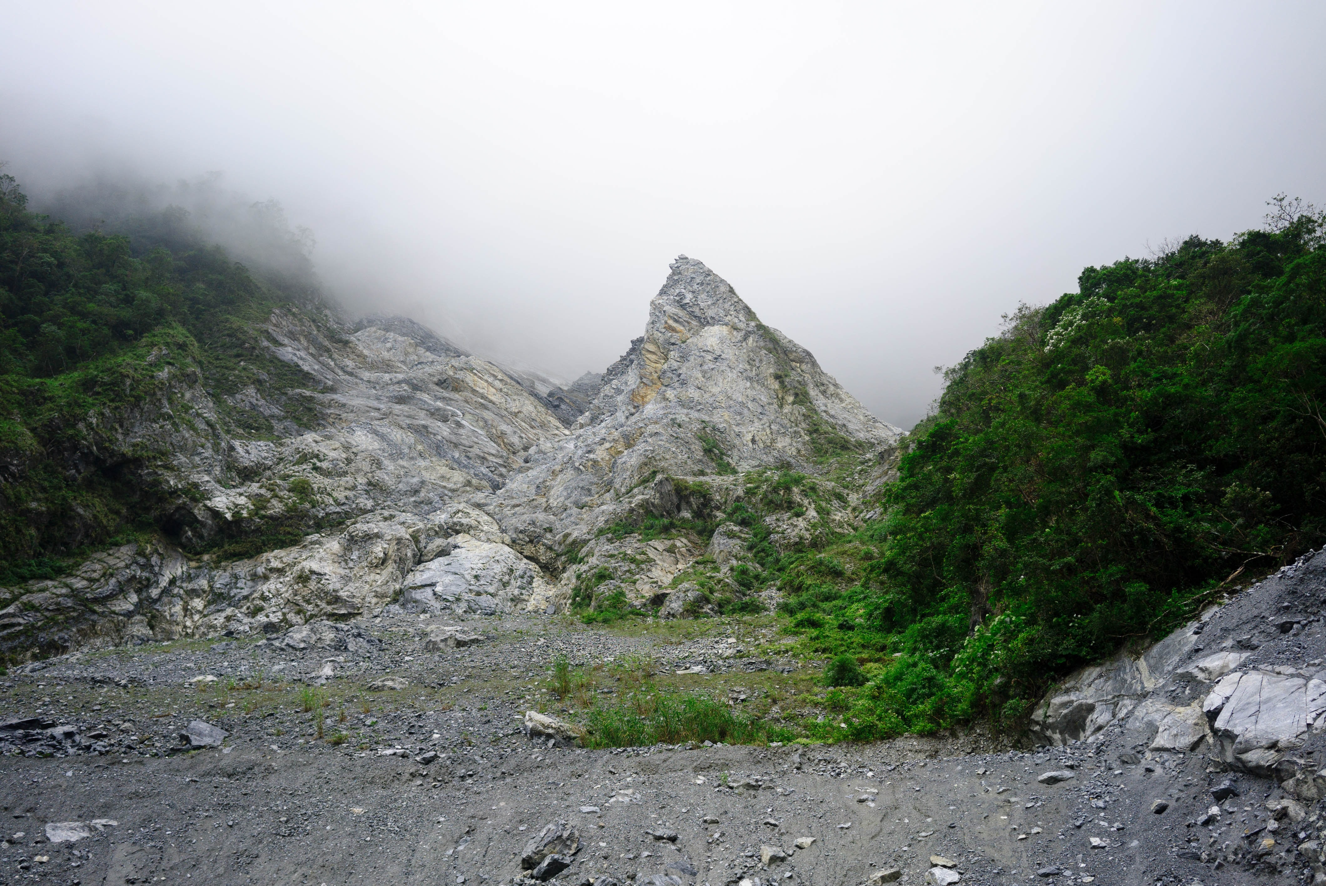A craggy rock formation with a sharp peak on a mountainside