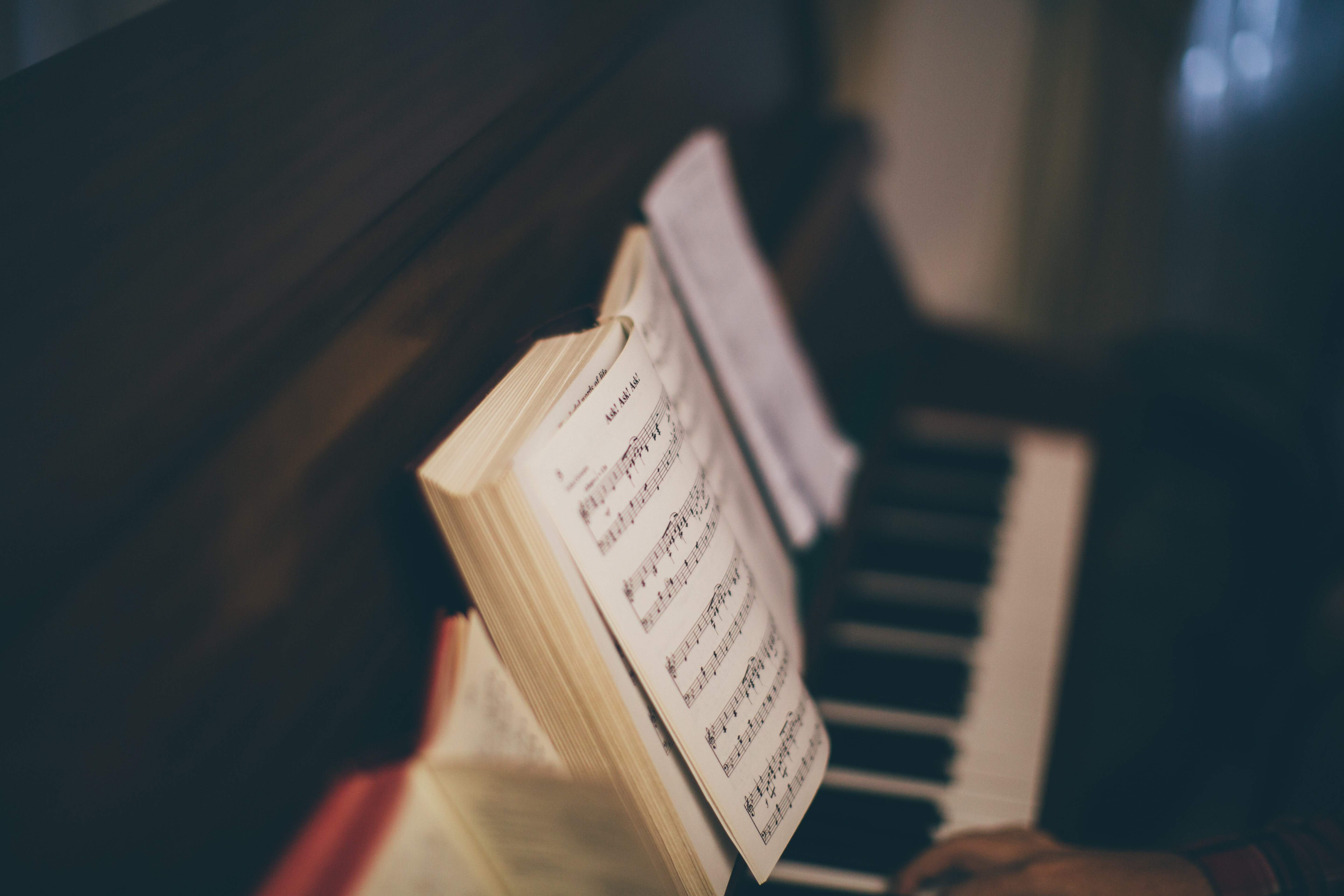 opened music sheet book on top of upright piano