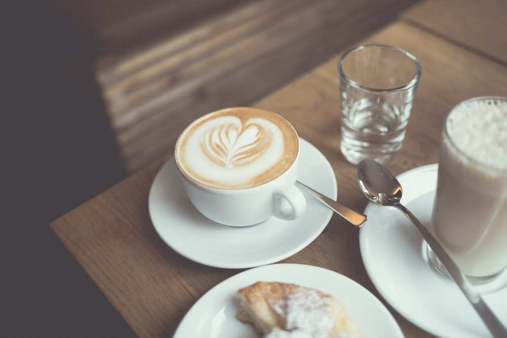 white cappuccino coffee near clear drinking glass