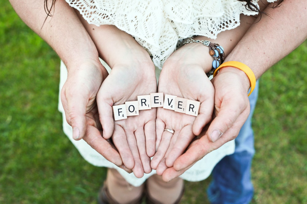 adult and girl holding forever scrabble letters during daytime