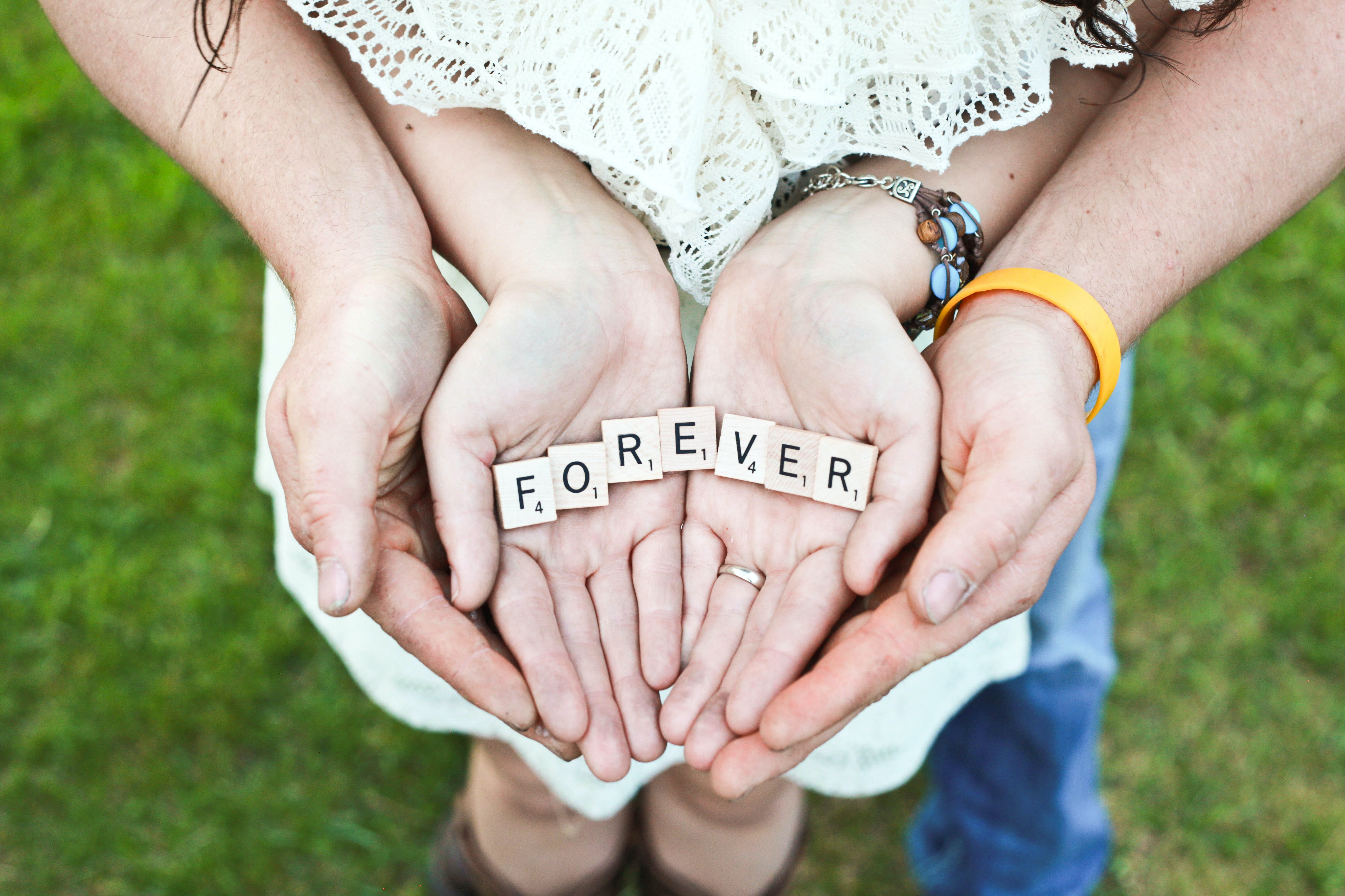 "A couple's hands hold up Scrabble letters spelling out ""FOREVER"""
