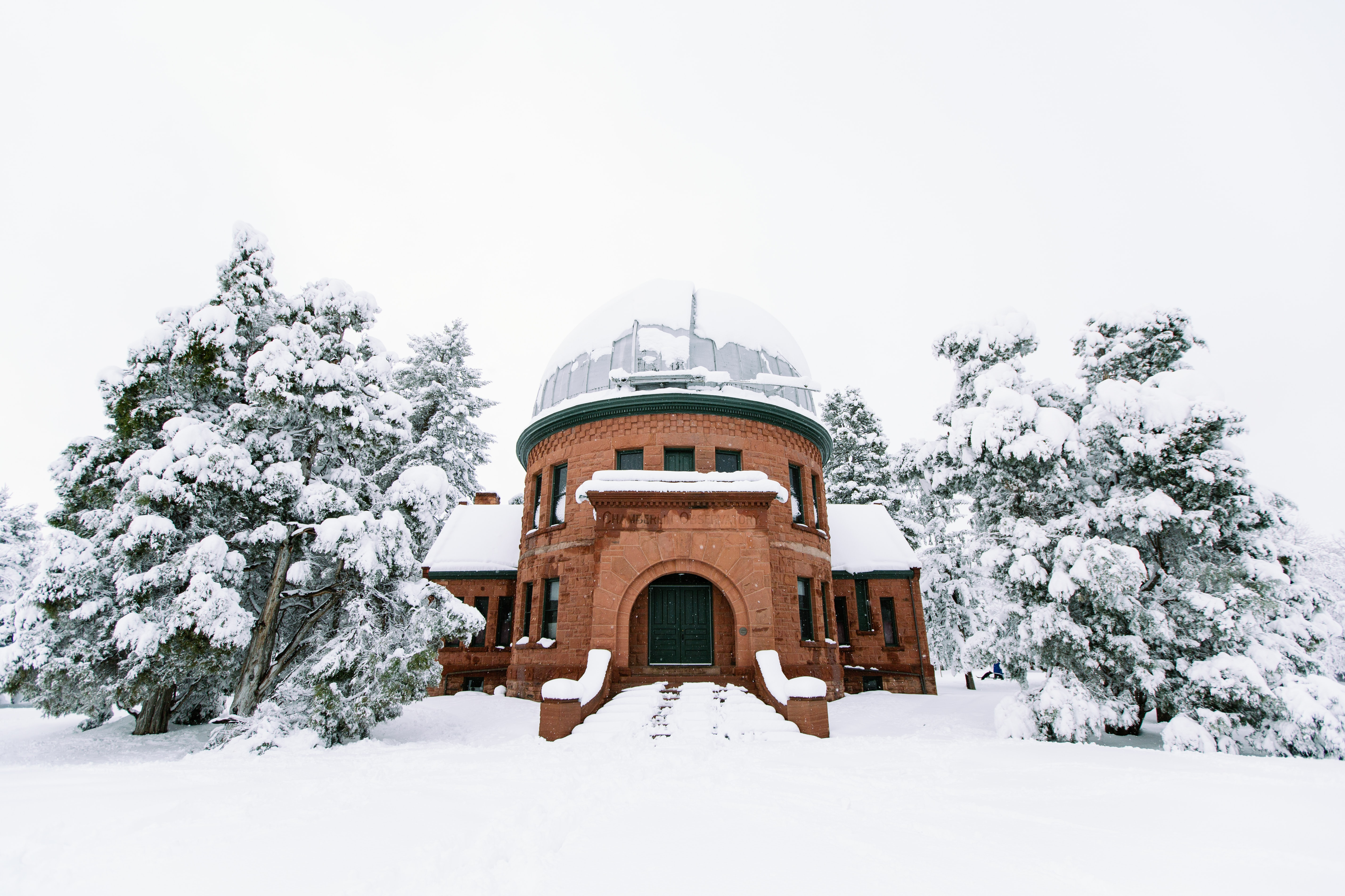 A building in the snow surrounded by wintery trees