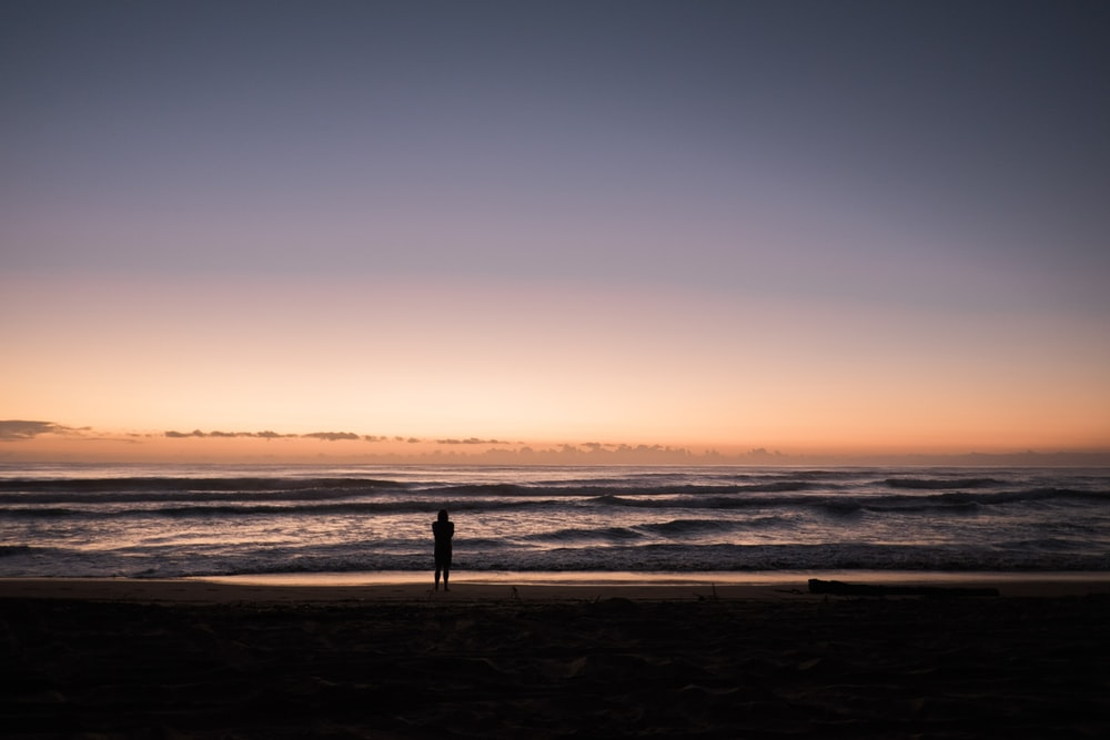person in the beach during sunset