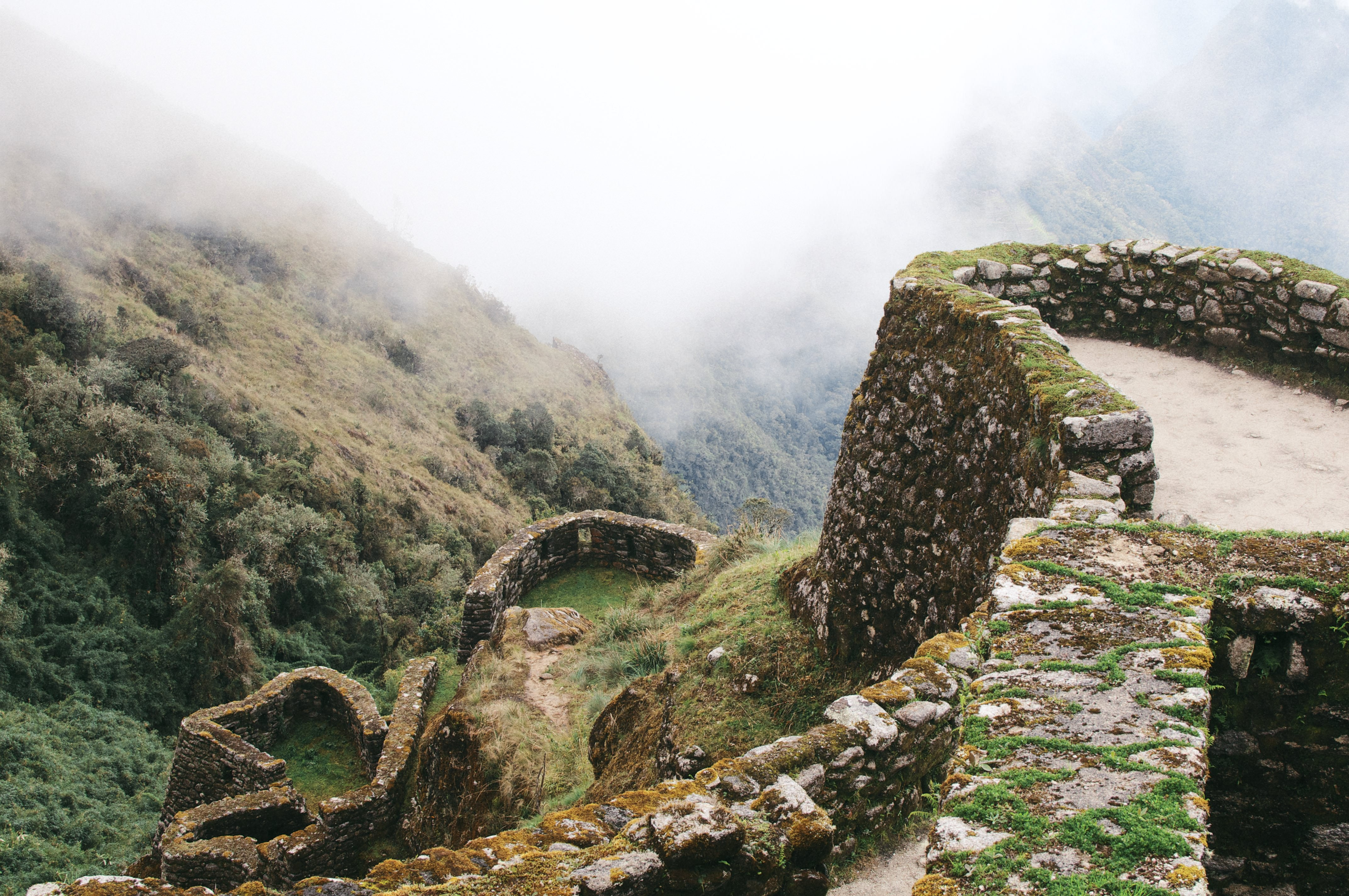 Rocky Inca ruins covered in moss on a misty mountain