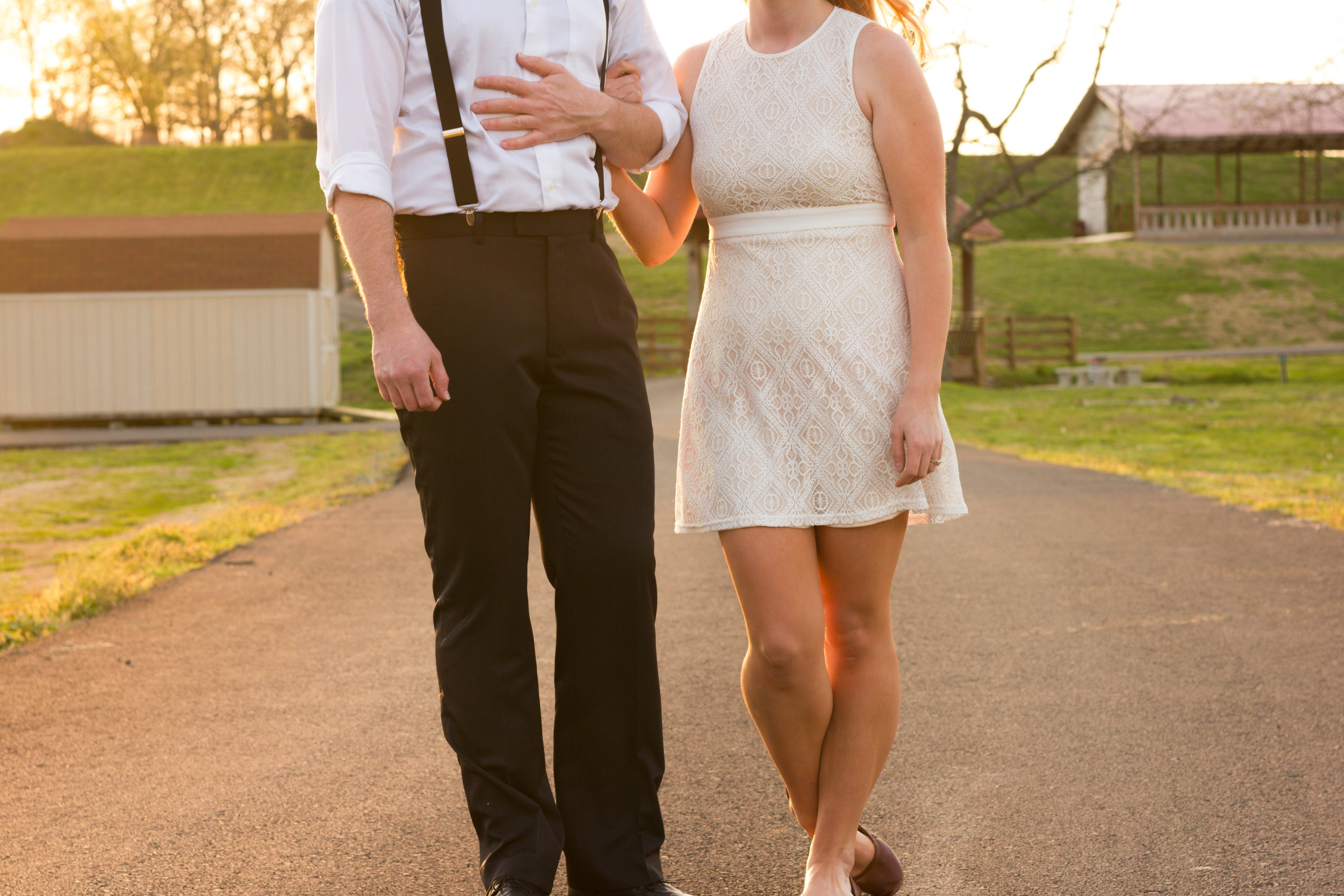 A couple in formal wear stands next to each other on a path in a park in Chattanooga