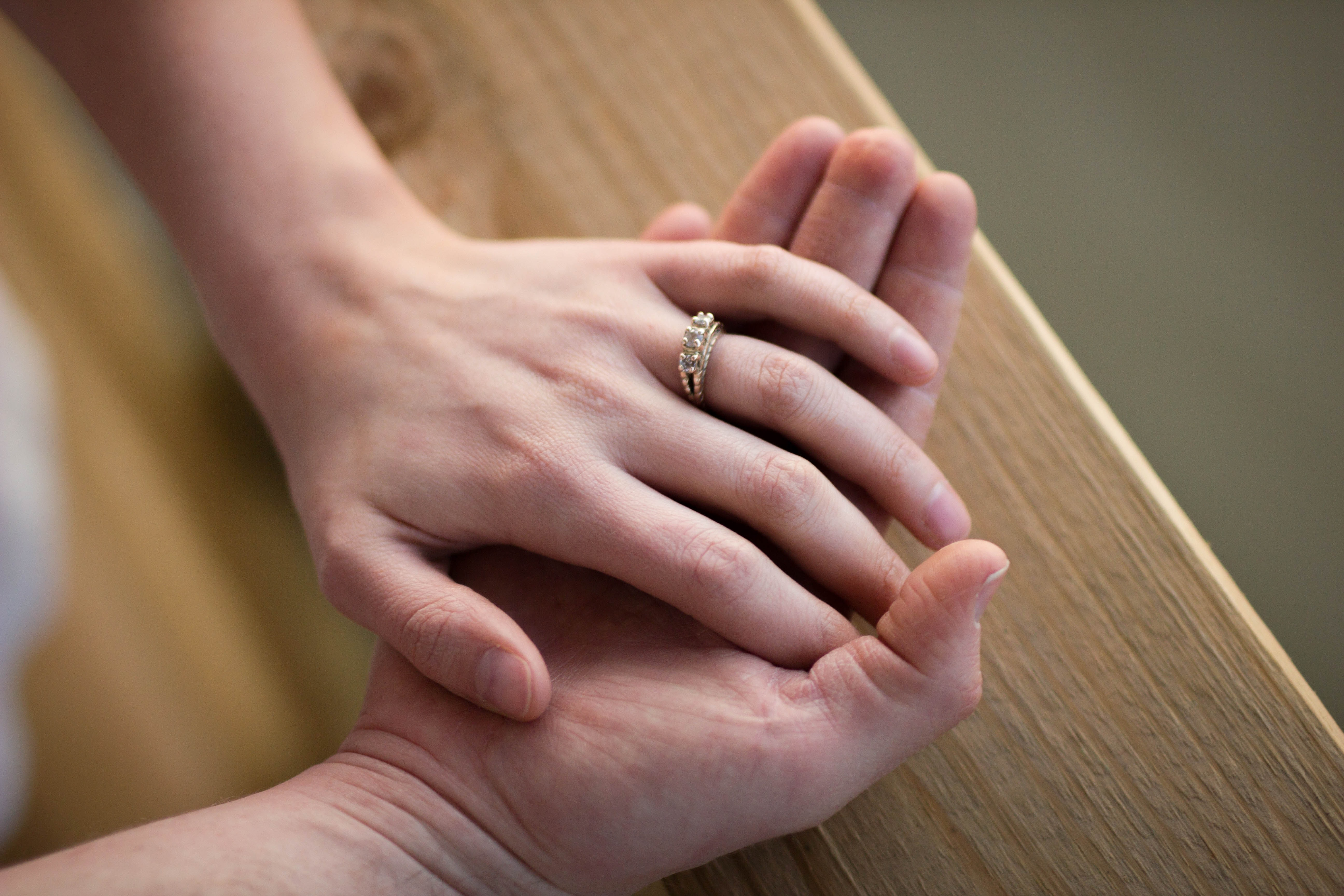 Bride's hand wearing wedding ring sits on groom's hand in Chattanooga
