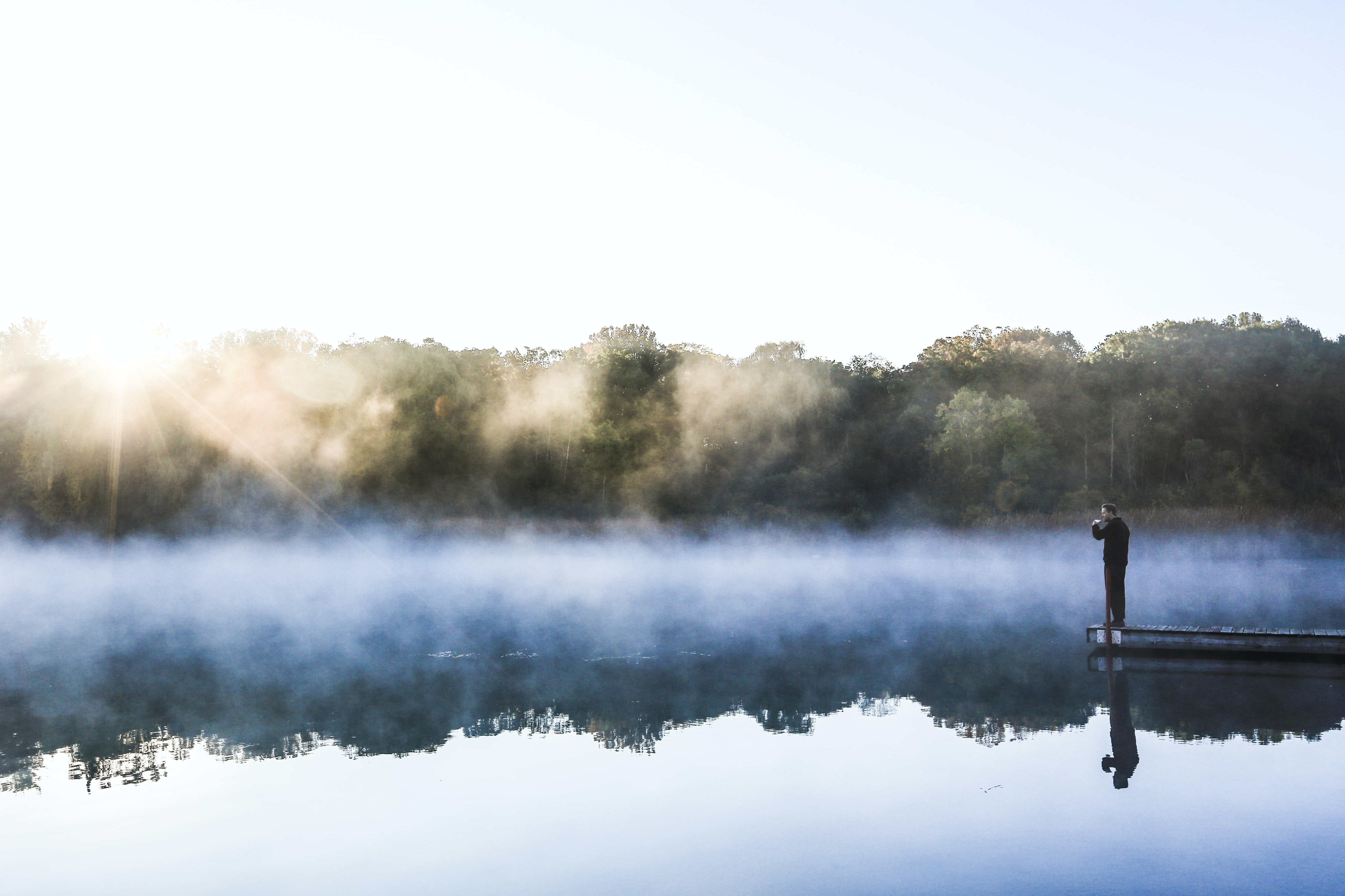 Person standing on the end of a pier looking out at a calm foggy lake