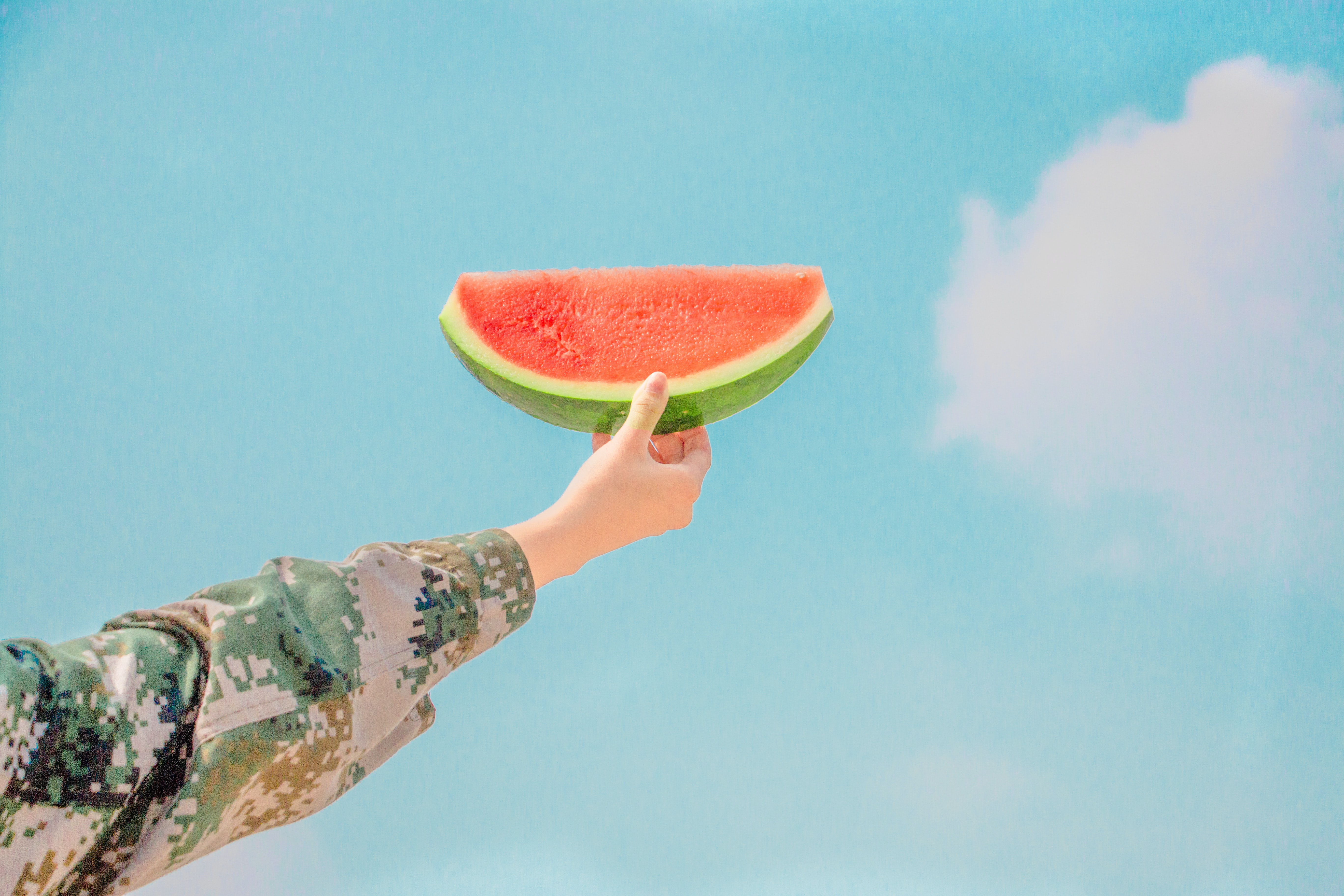 Person wearing a camo holds a piece of watermelon to the blue sky