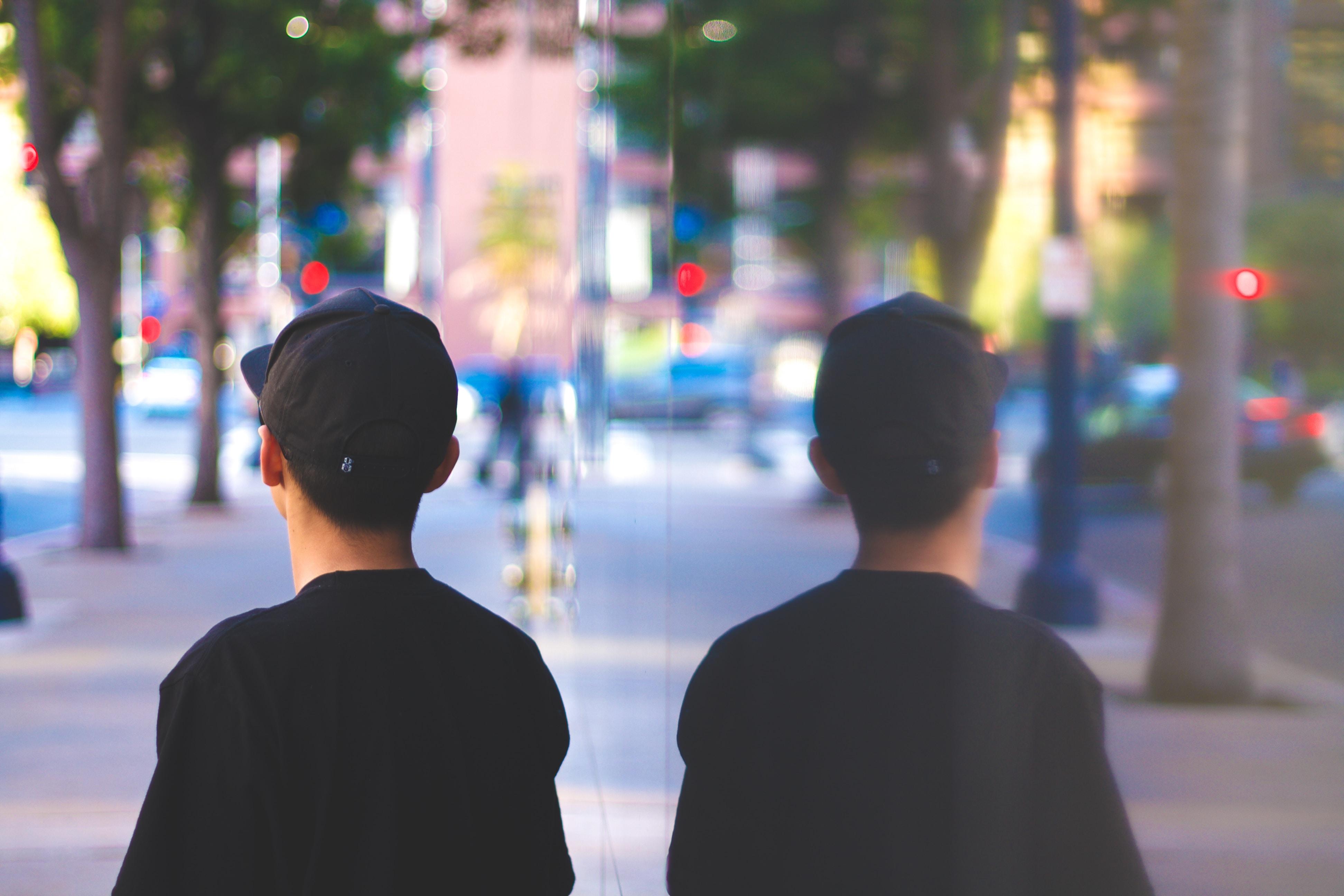 A reflection of a boy wearing a baseball cap standing on a sidewalk
