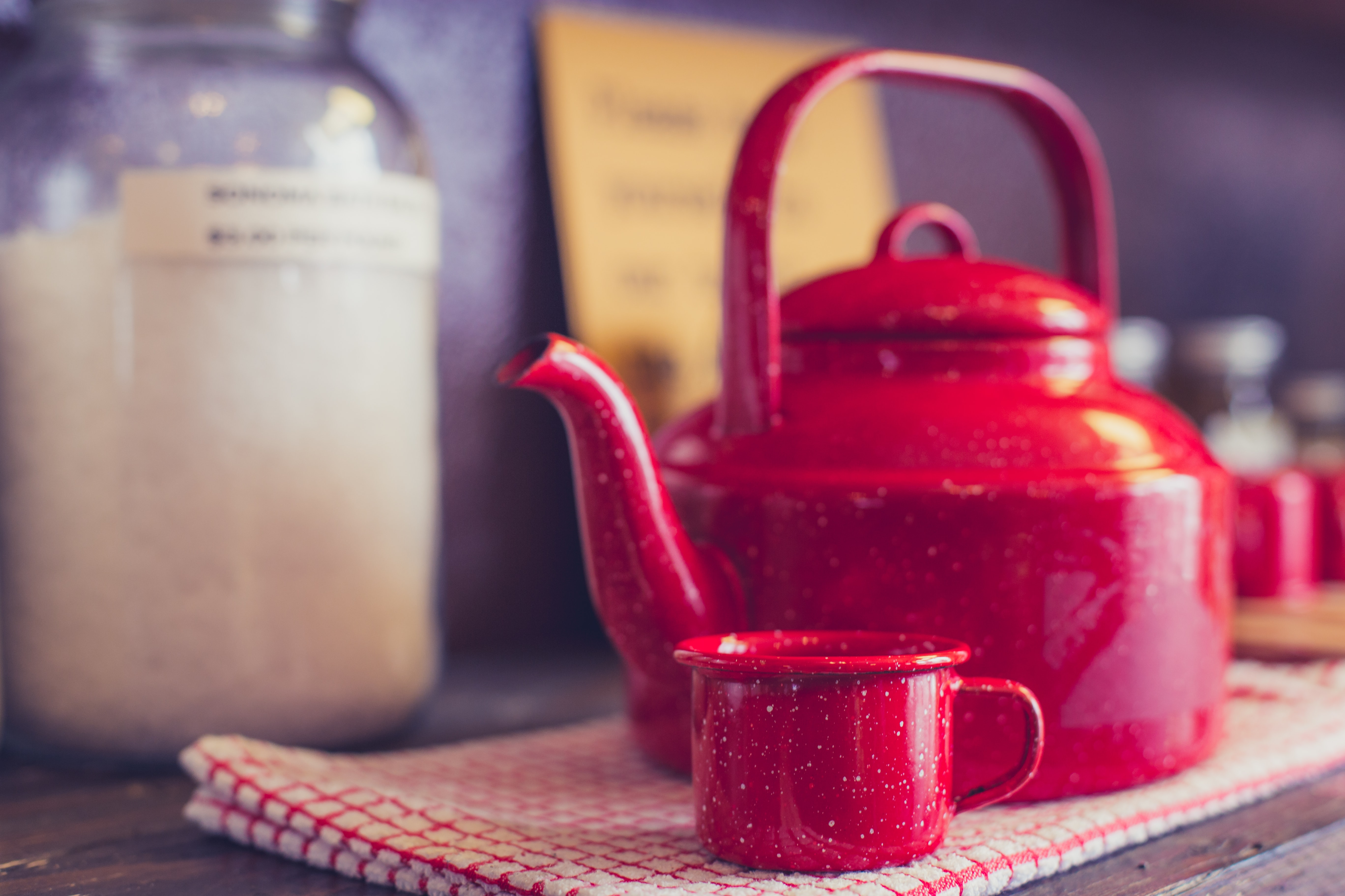 Red tea kettle with a red tea cup next to it on a red and white gingham cloth and kitchen wall in the background
