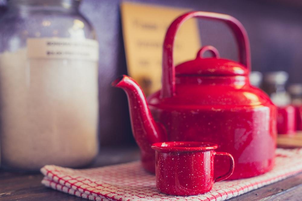 背景に赤と白のギンガム布とキッチンの壁の上にそれの隣に赤いお茶のカップと赤茶のケトル