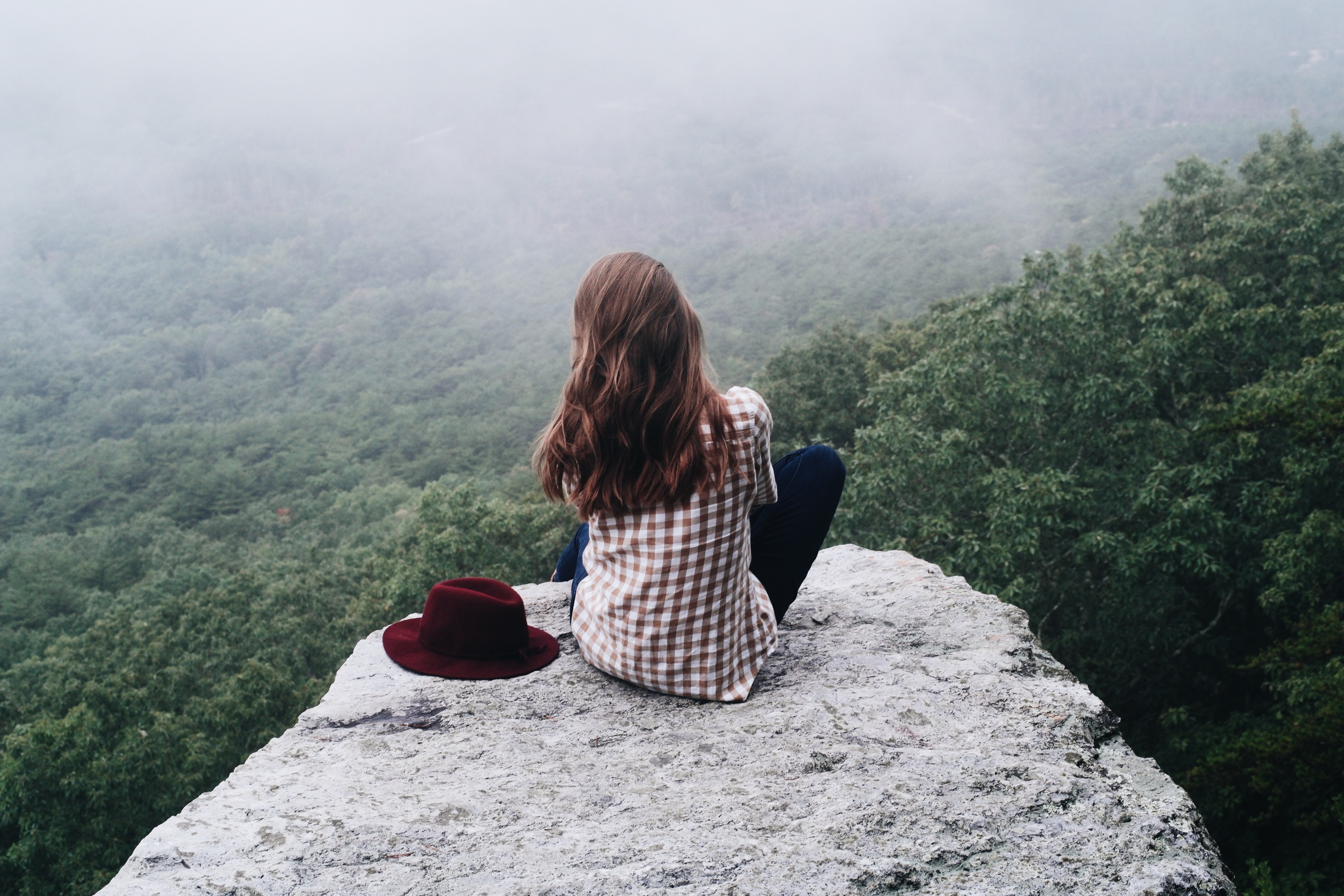 woman sitting on top of gray rock