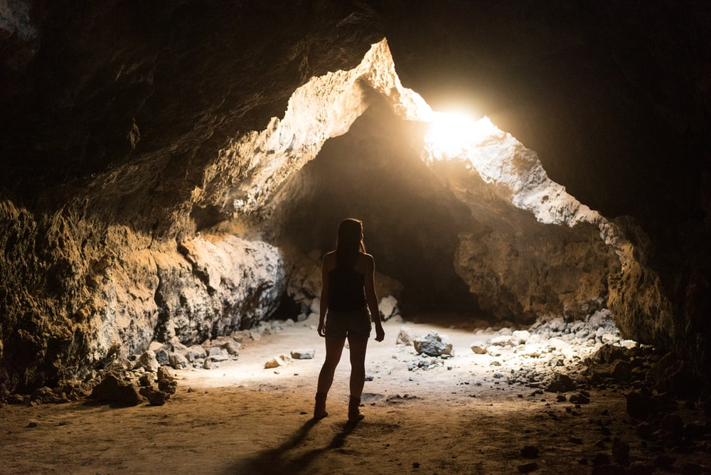woman standing inside cave