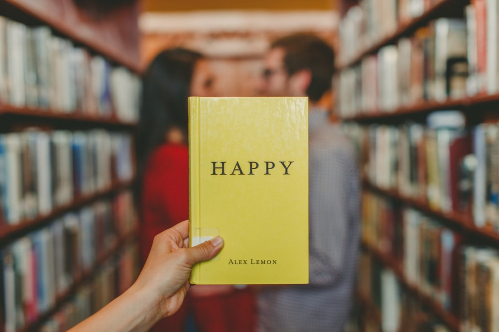 person holding Happy by Alex Lemon book
