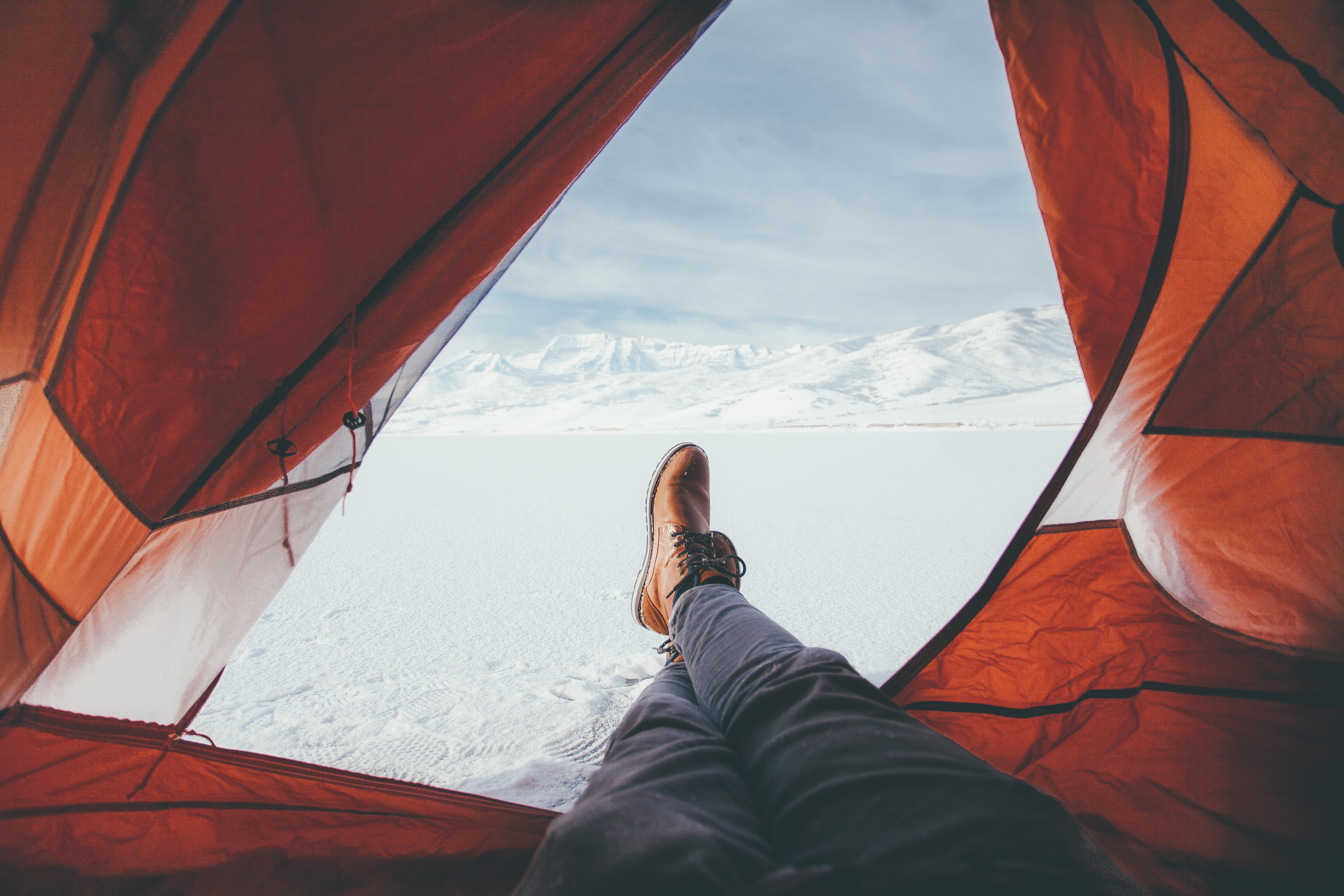A person in a tent with their feet out the opening camping on a snow covered mountain in Deer Creek Reservation.