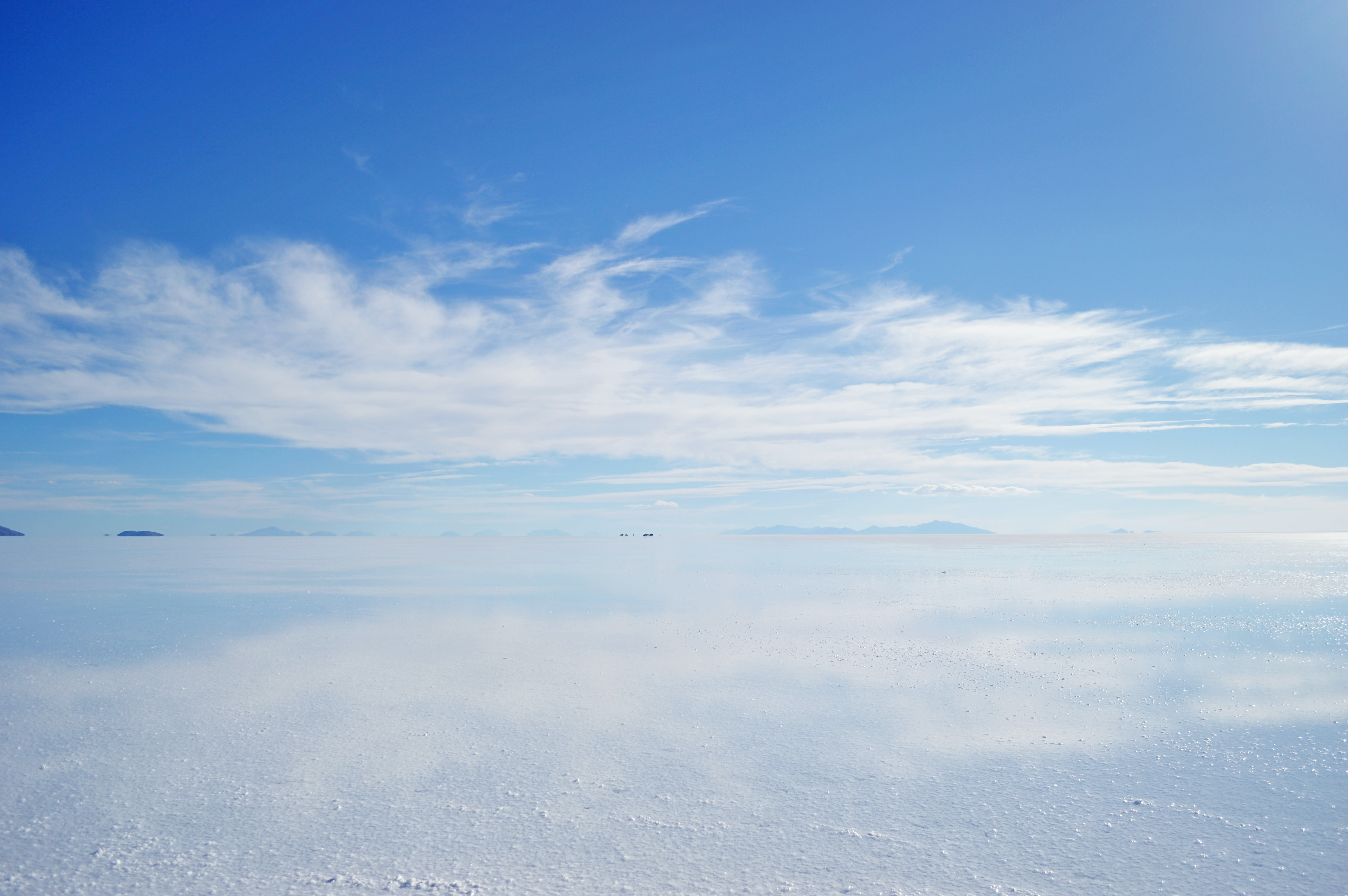 White sand blends into the horizon of a cloudy sky in a desert in Uyuni
