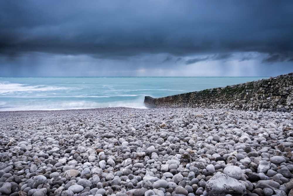 body of water across pebbles under dark sky