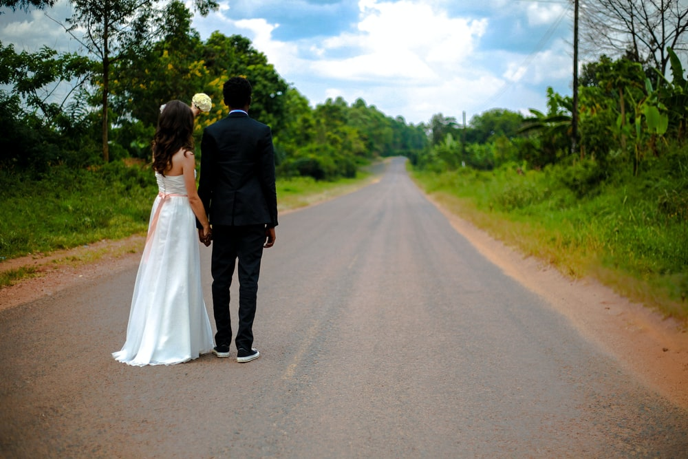 wedding couple standing on winding road between trees under cumulus cloud