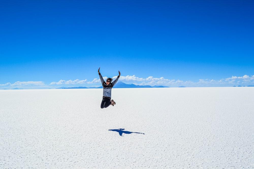 woman jumping under blue skyt
