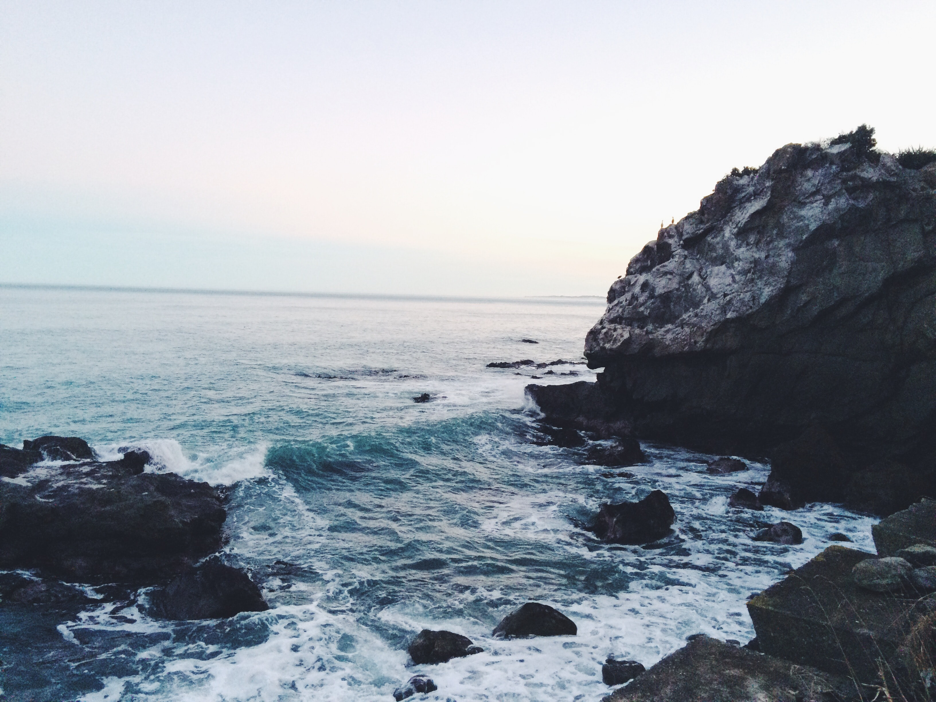 ocean waves near rocks during daytime