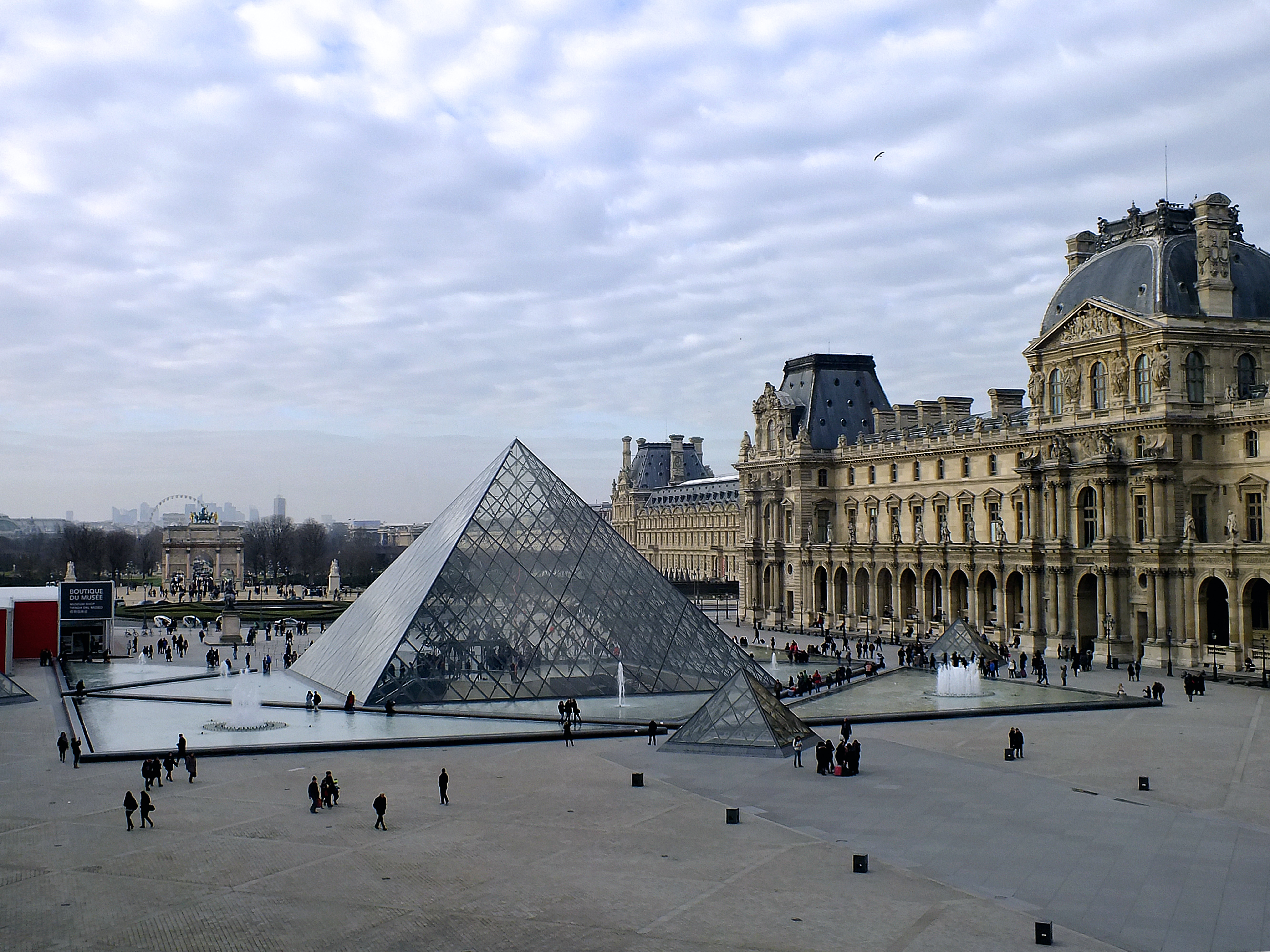 Tourists with the landmark pyramid outside the Louvre museum in Paris, France.