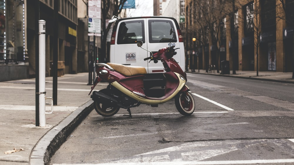 red and beige motor scooter