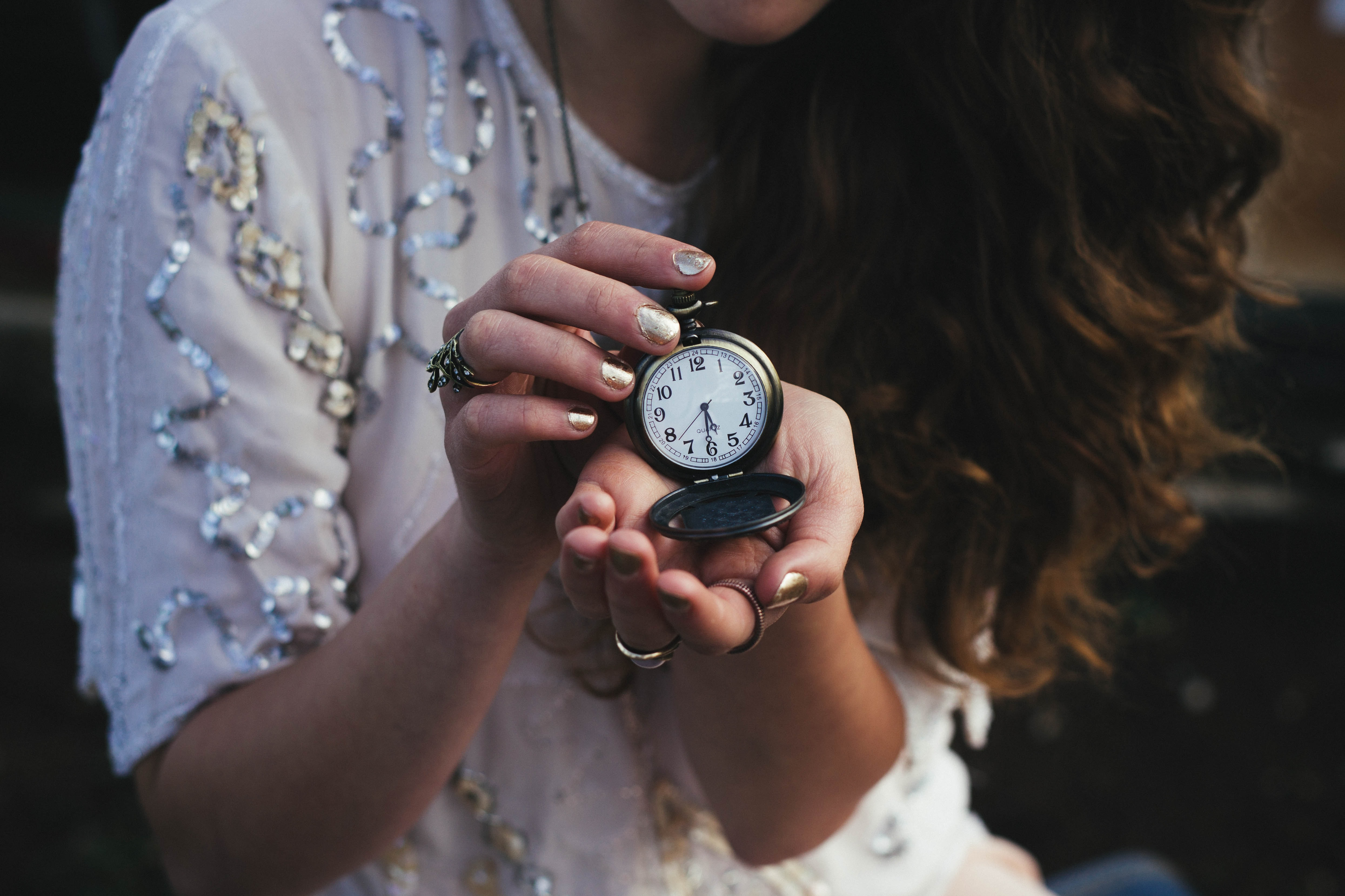 woman holding black pocket watch at 5:30