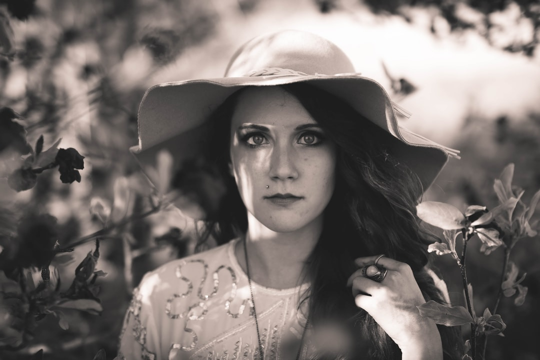 Black and white shot of attractive dark haired woman in large floppy hat amongst plants, Benton