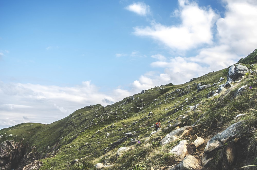 person walking on mountain during daytime