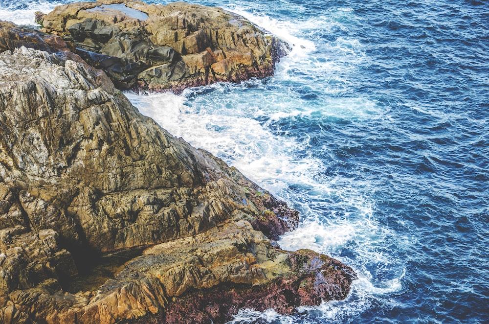 aerial photo of sea waves splashing through rocky mountain