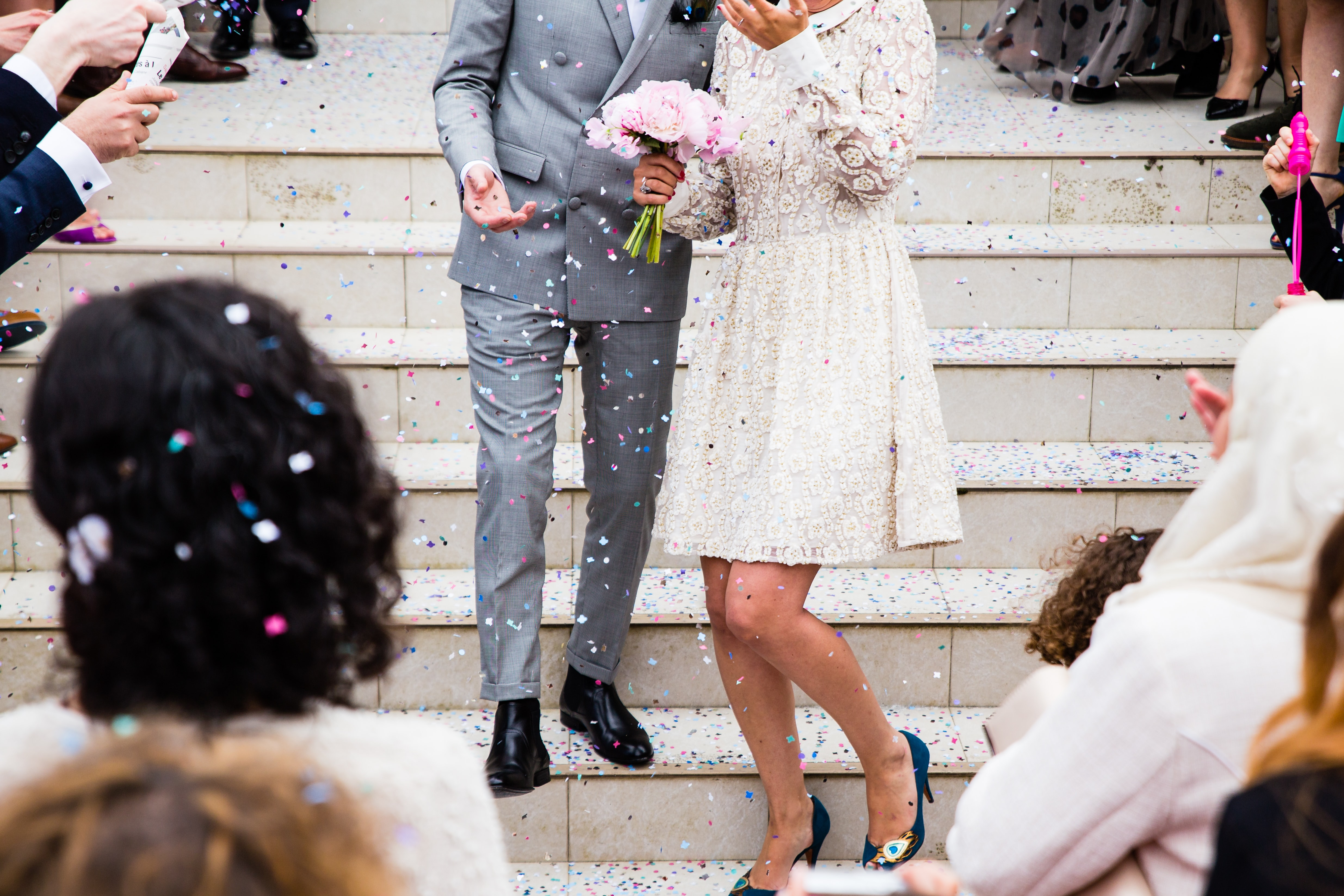 Crowd of well-wishers throws glitter onto newlyweds descending a staircase