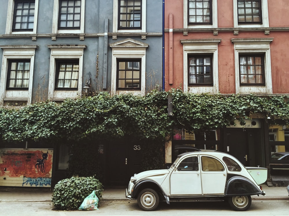 white car parked beside brown building