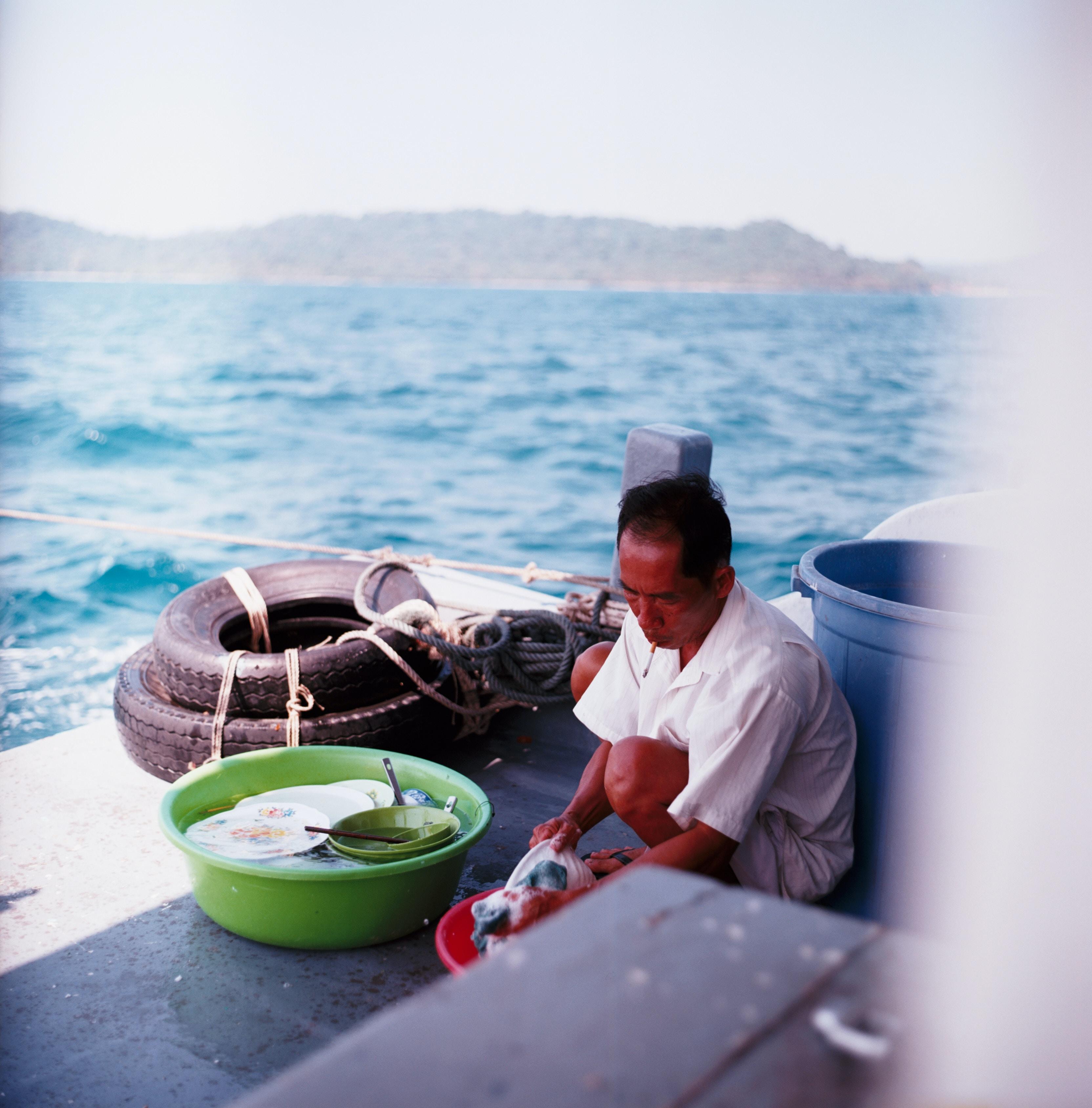 man washing dishes beside blue plastic pail