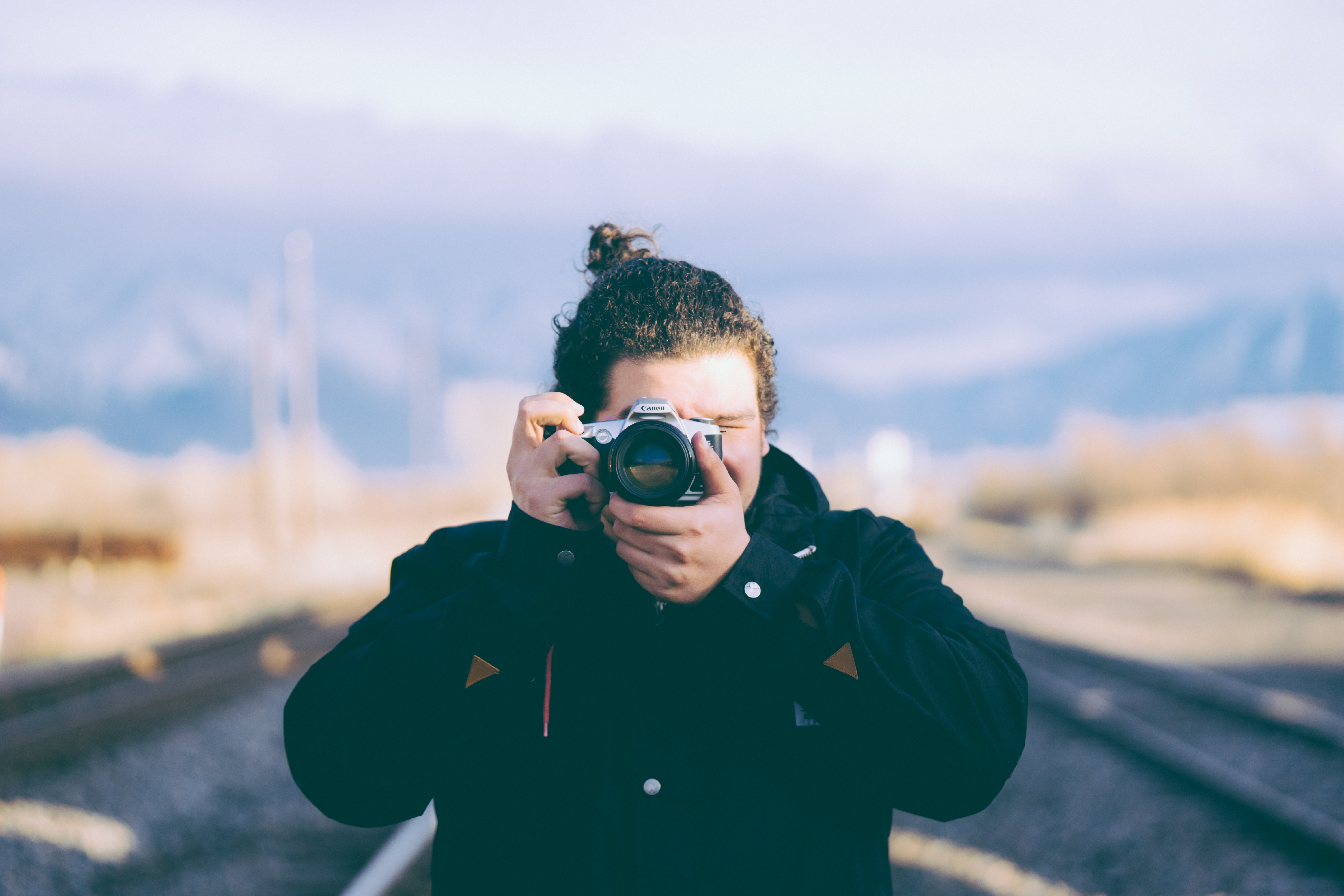 selective focus photography of man holding camera taking photo