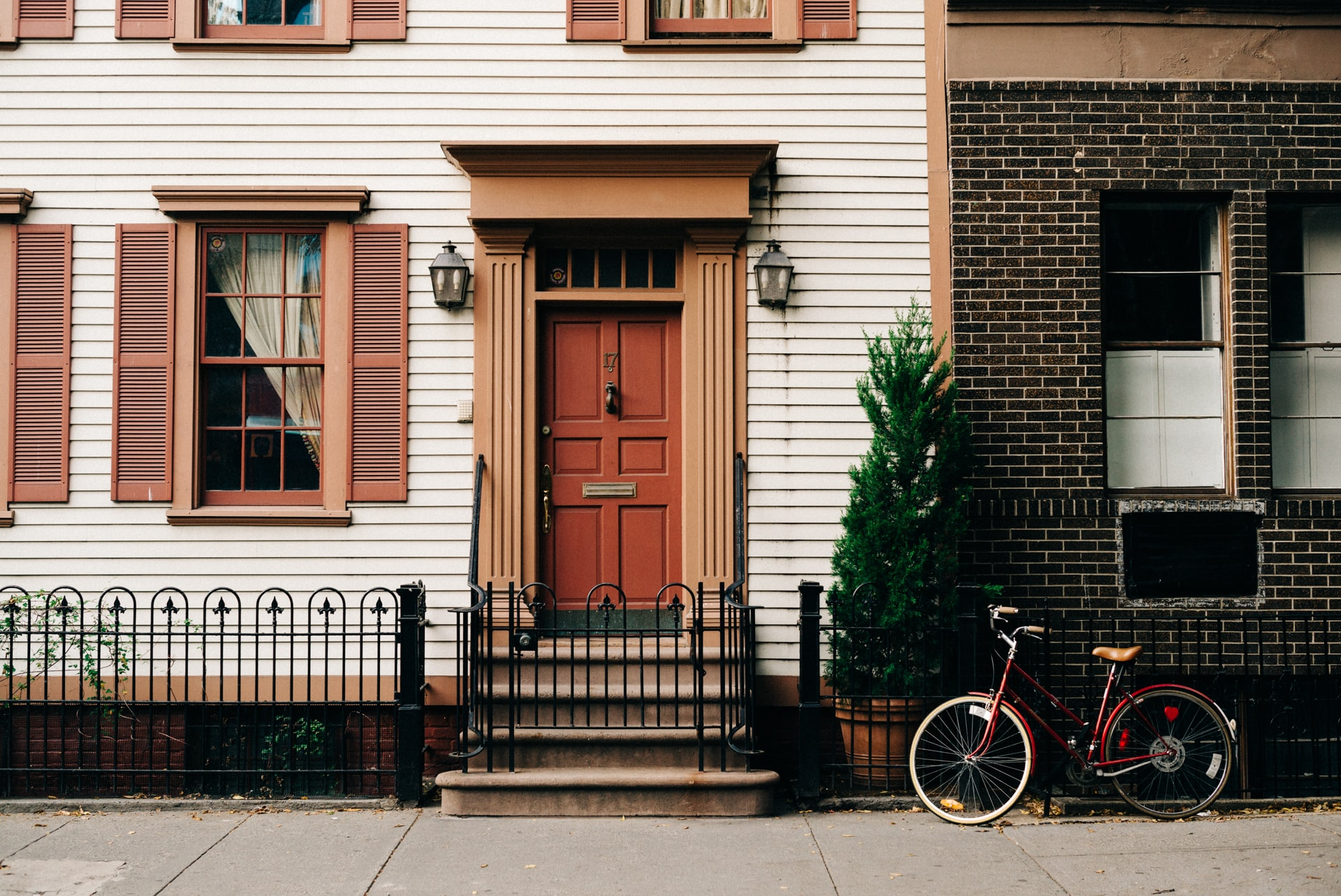 red bicycle parked beside black metal gate in front house