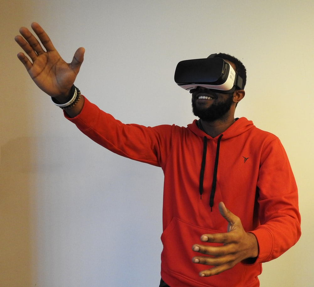 man wearing white VR headset while lifting right hand