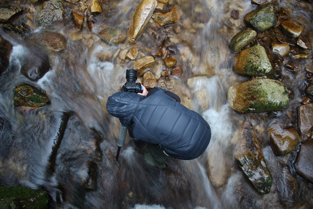 man standing on stream