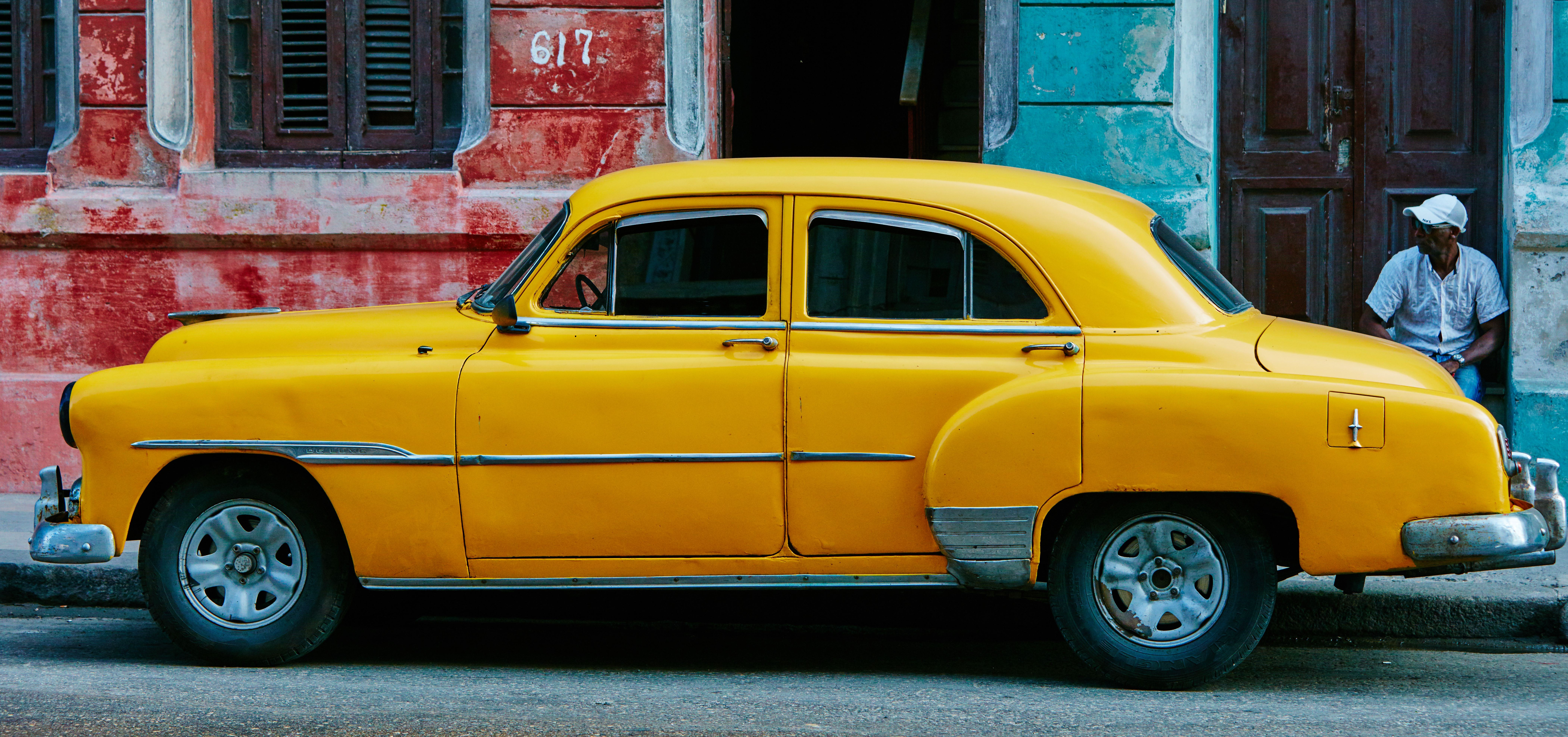 Parked vintage yellow car on street in Havana with an onlooking man in the background