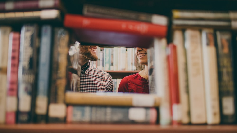 A picture of a smiling couple taken through books at the Berkeley Public Library