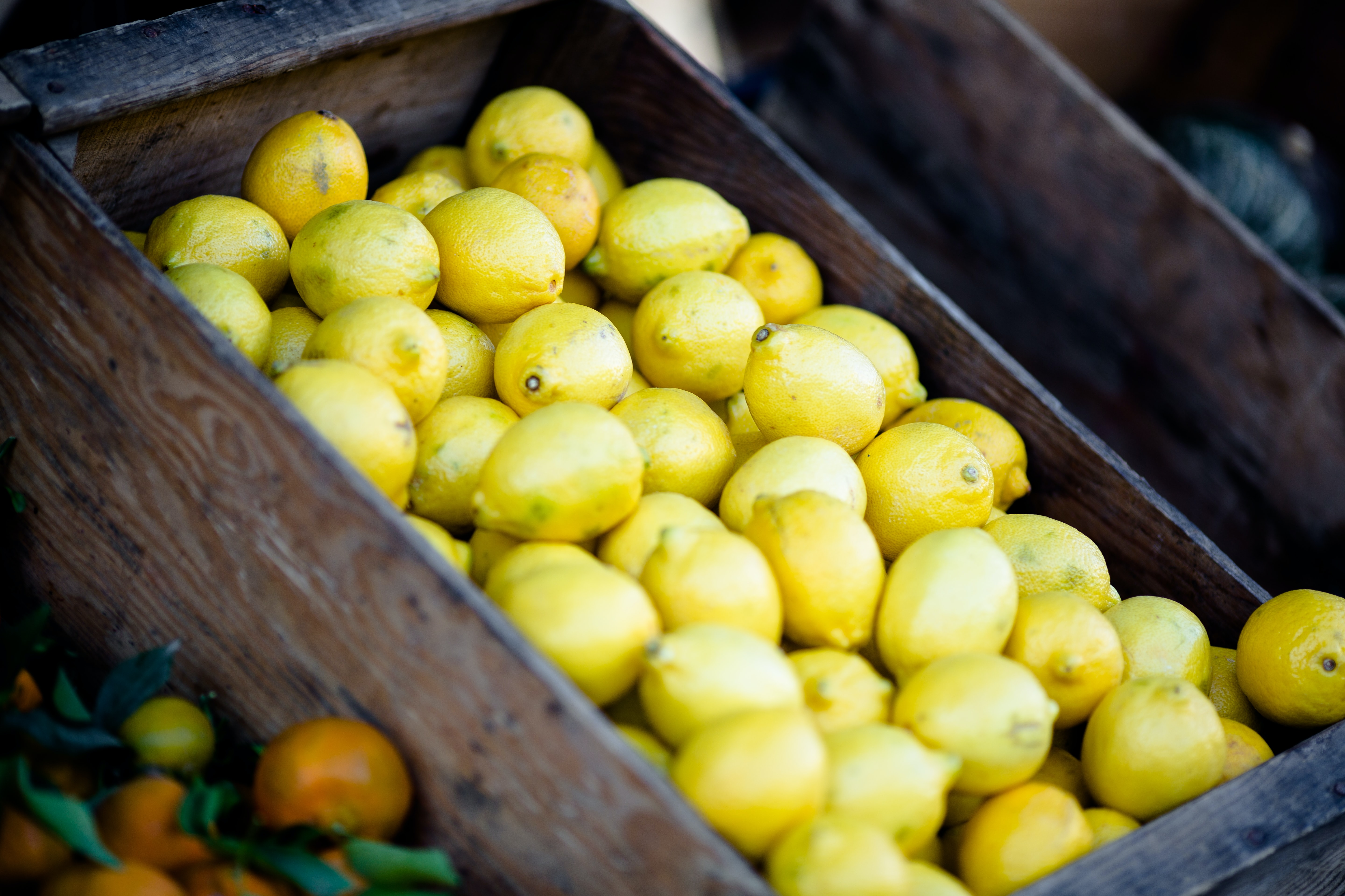 Wooden crates of fresh lemons at a fruit vendor