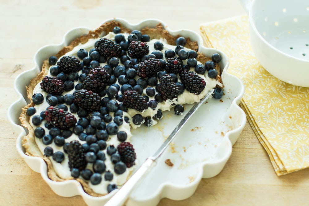 blueberry pie on plate with knife