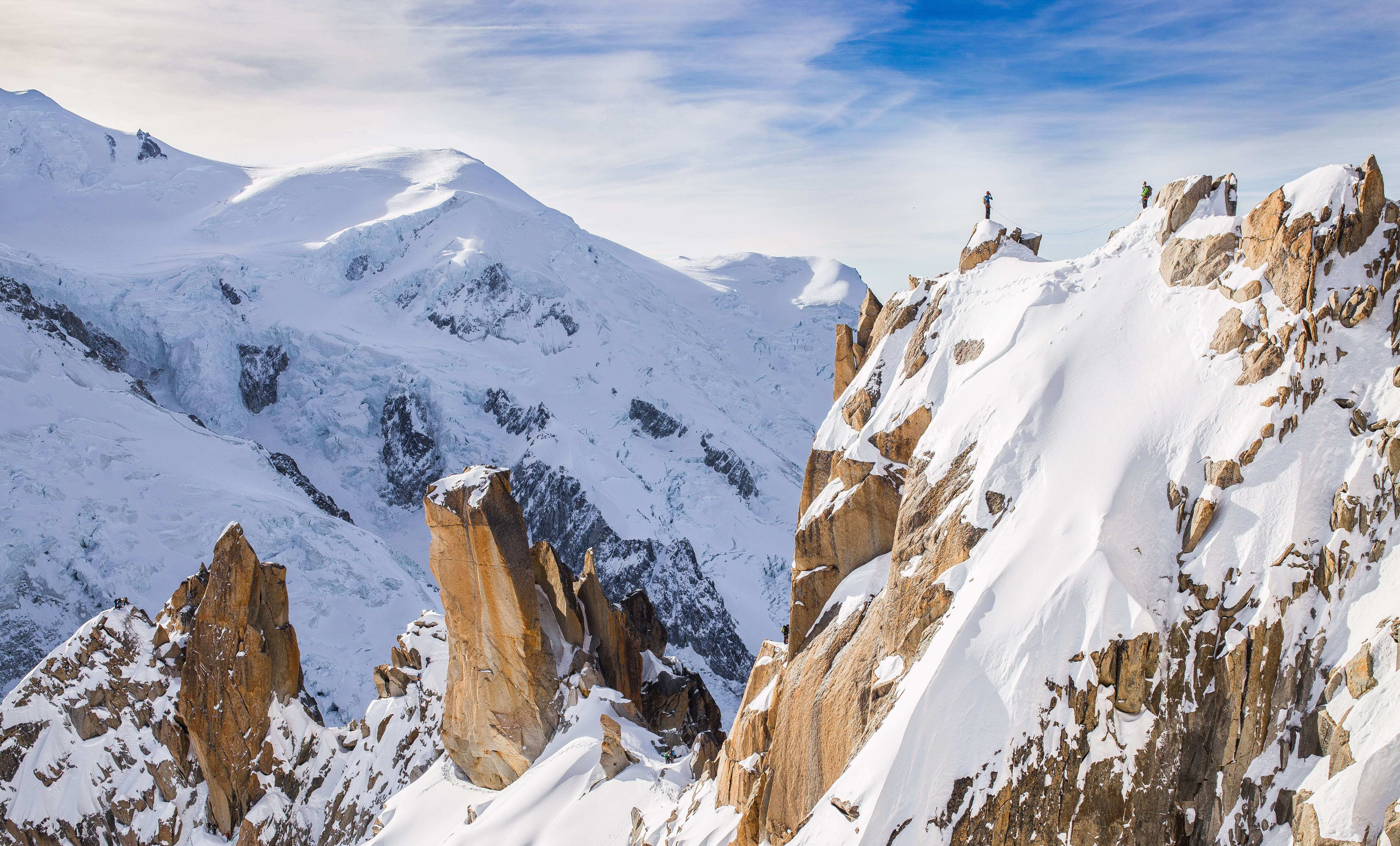 A hiker on a jagged mountain peak covered in snow