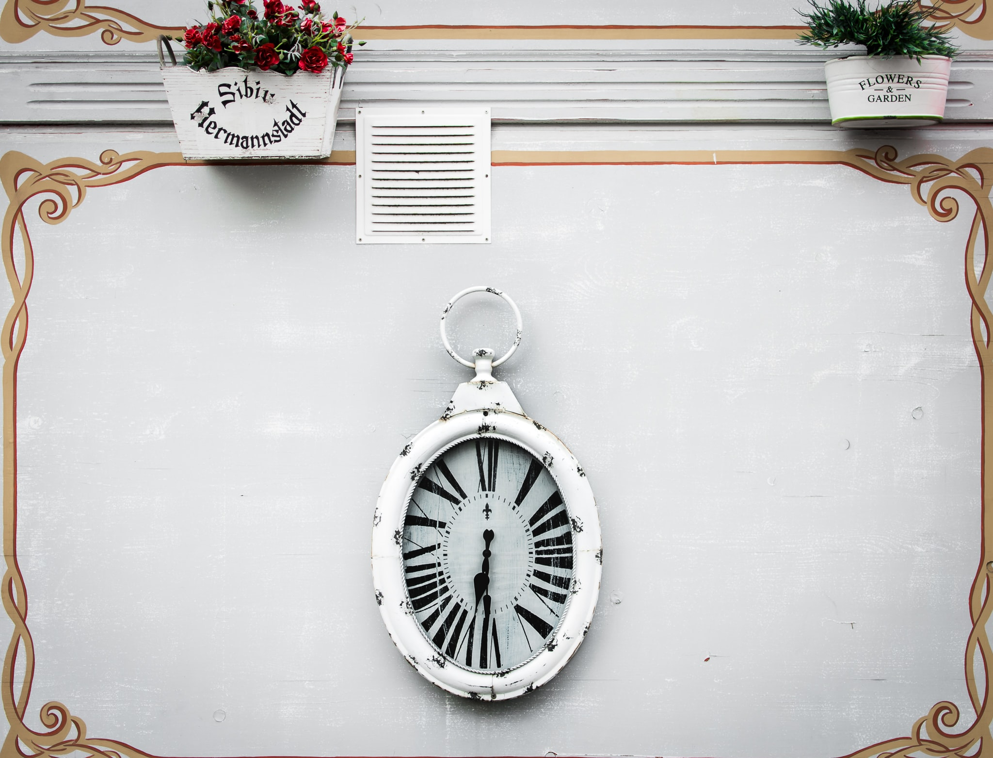 oval white analog clock display at 6 o'clock
