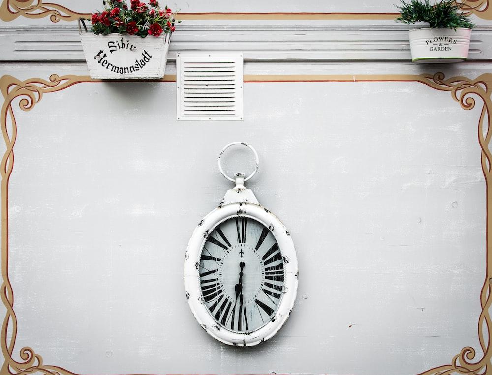 oval white analog clock display at 6 o'clock