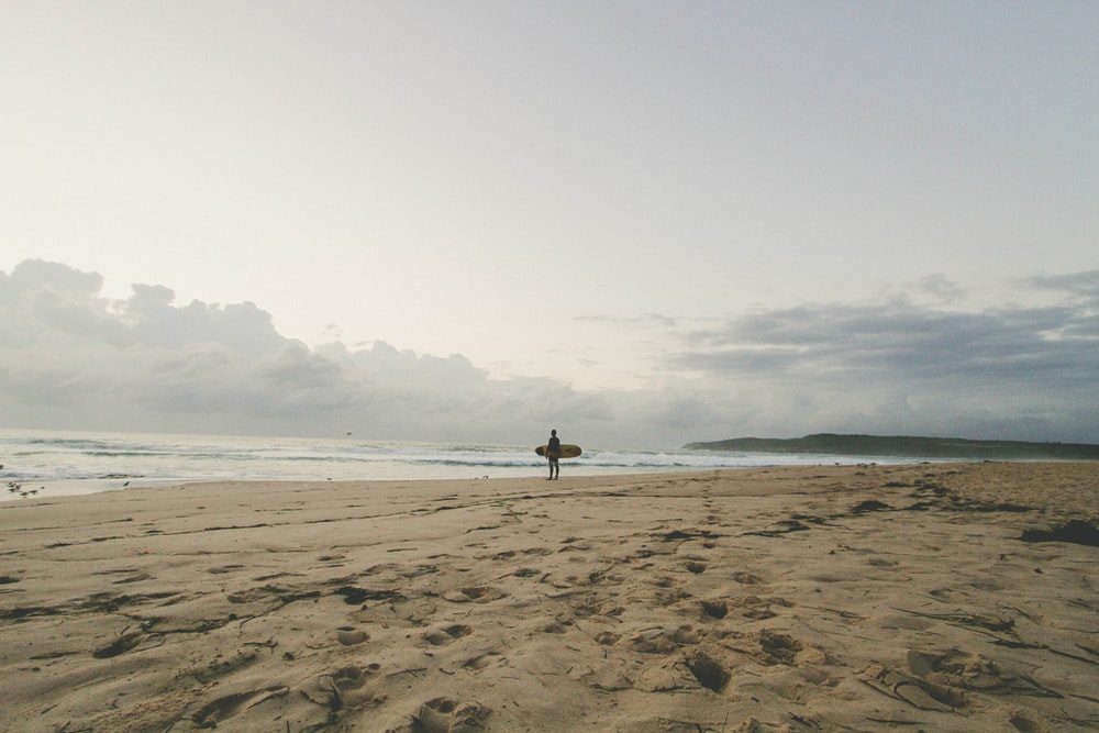man standing by the seashore with surfboard