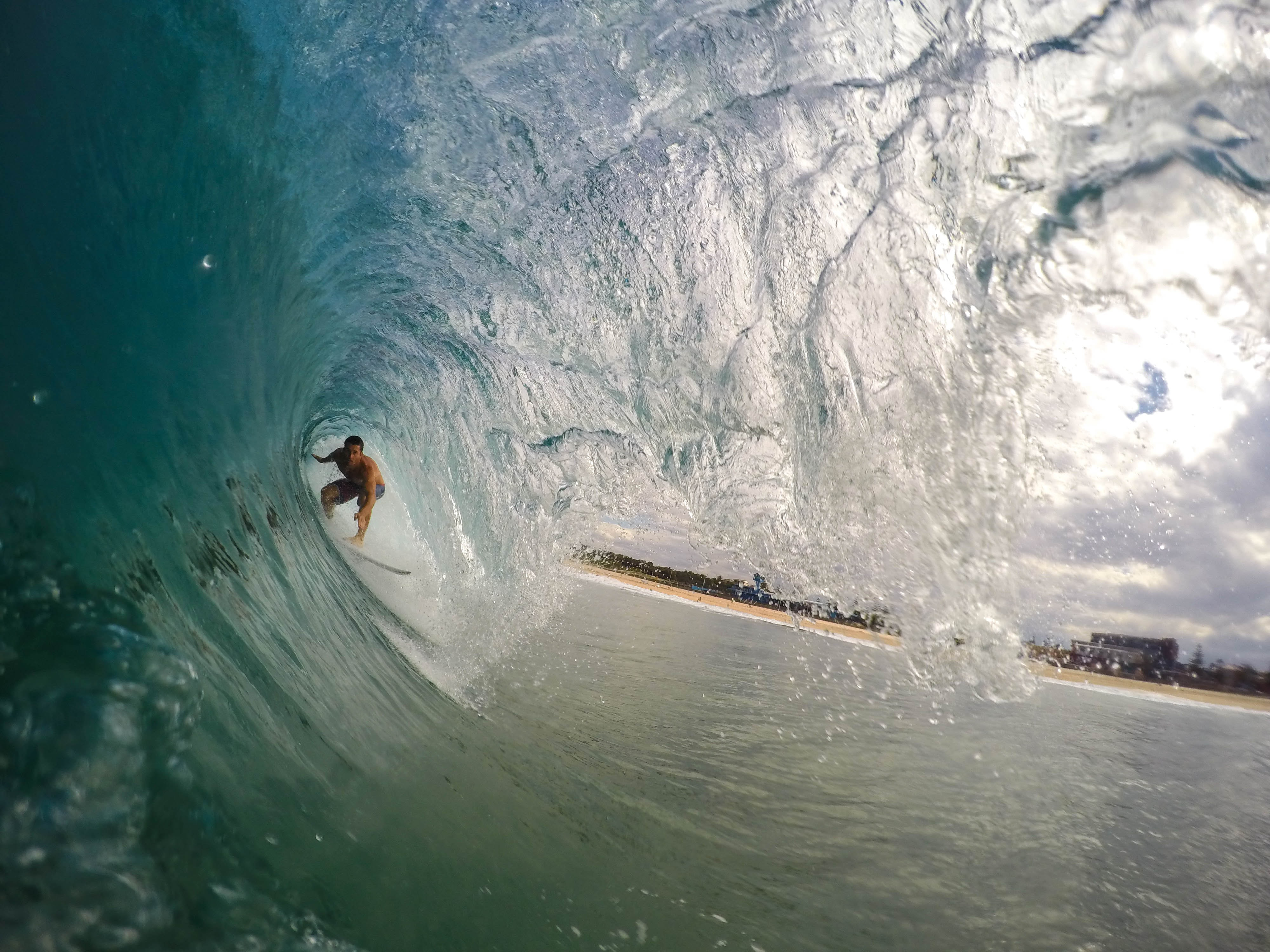 A surfer riding a large wave near a beach