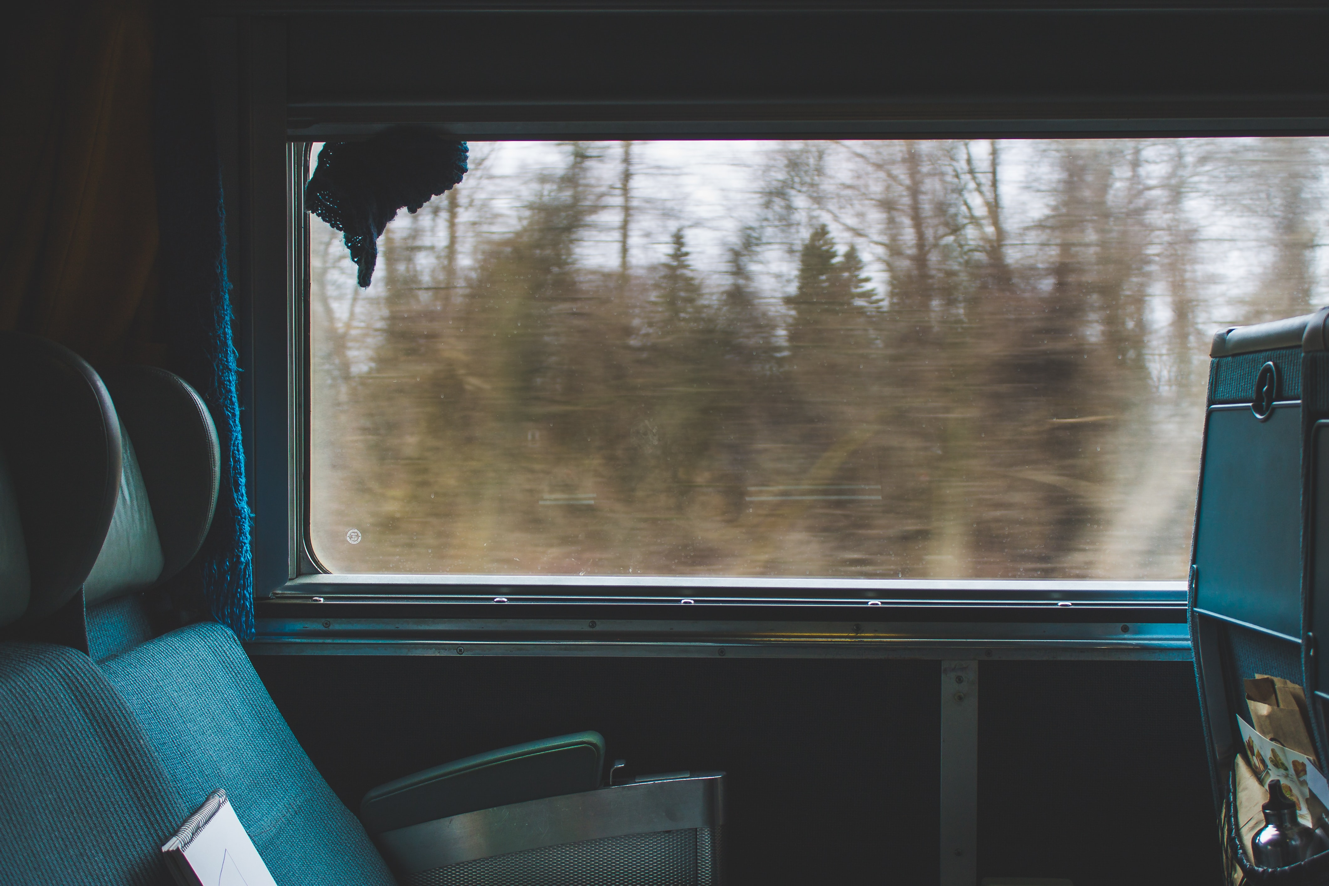 The interior of a moving train with empty seats next to a window